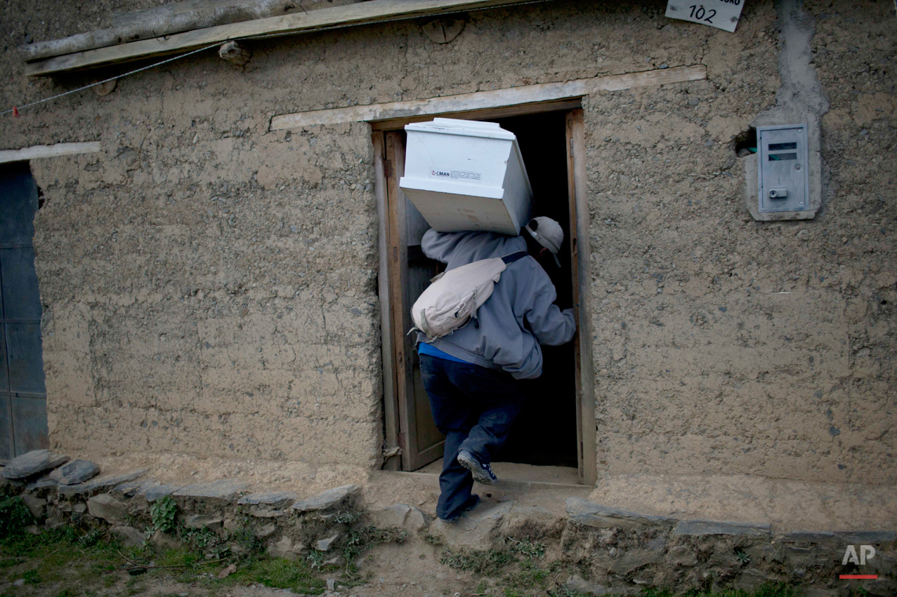 In this Oct. 28, 2014 photo, Victor Crisostomo, carries the remains of his brother-in-law Nestor Curo Palomino into his home for a one day wake in Huallhua, in Peru's Ayahuanco region. The remains of Curo, who was in his 20s when he was killed defending the town with two other members of the village's citizen self-defense force from Shining Path militants on June 14, 1990, were exhumed and handed over to relatives last week. (AP Photo/Rodrigo Abd)