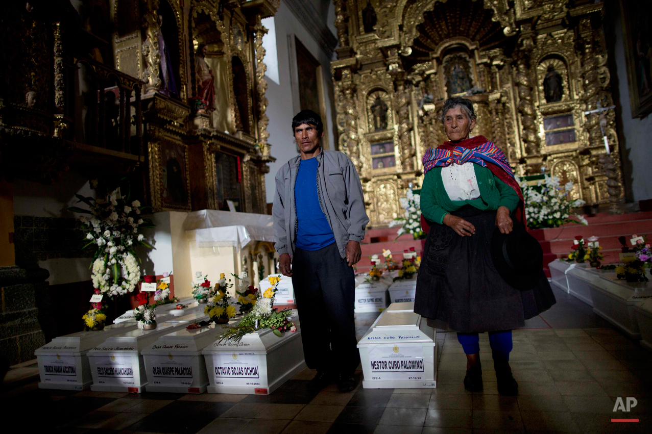 In this Oct. 27, 2014 photo, Eusebia Palomino Arona, 88, right, and her son-in-law Victor Crisostomo, left, stand next to the coffins of Eusebia's son, Nestor Curo Palomino, as they pose for a portrait to document the funeral after Mass in Huallhua in Peru's Ayahuanco region. Curo's remains were exhumed last year and recently handed over to relatives, allowing them to bury him properly 24 years after he was killed on June 14, 1990 defending their town so villagers could escape from Shining Path militants. He was in his 20s. (AP Photo/Rodrigo Abd)