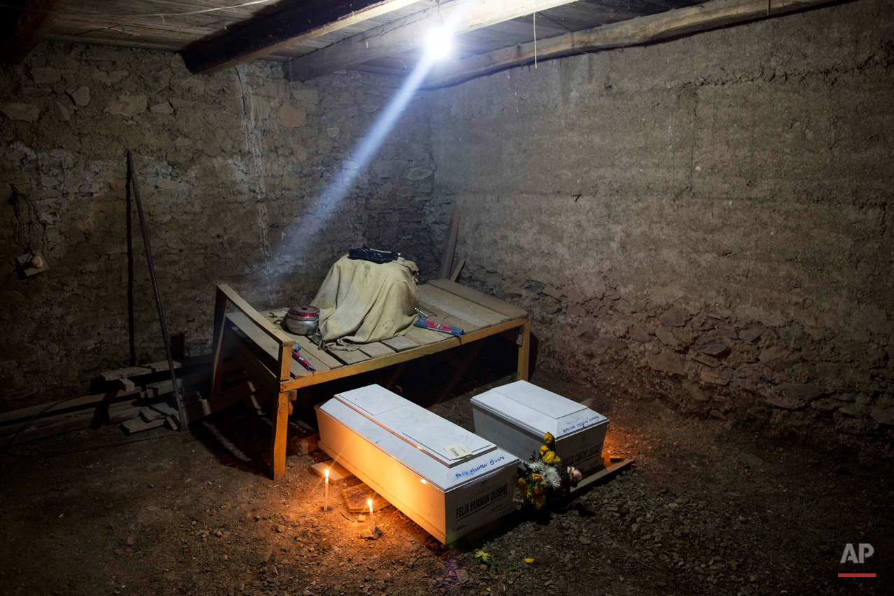 In this Oct. 29, 2014 photo, a lamp shines inside the dirt floor home of the Huaman family where the coffins of Felix Huaman and his brother-in-law Narcizo Cusiche are placed for a one day wake, as is custom in Huallhua, Peru. Huaman and Cusiche were killed on June 14, 1990 defending the town as members of the citizen self-defense force so villagers could escape from Shining Path militants, but their remains were only recently exhumed. Hundreds of such cases, most until now barely registered, are coming to light as forensic anthropologists methodically unearth victims of Peruís 1980-2000 dirty war absent government fanfare. (AP Photo/Rodrigo Abd)