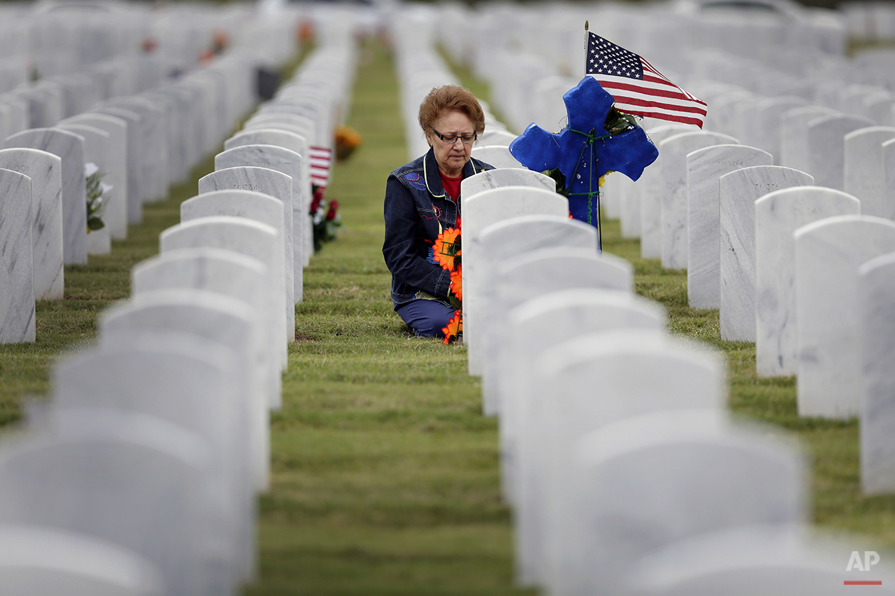 A woman knees at a headstone after placing an American flag and cross at Fort San Houston National Cemetery, Tuesday, Nov. 11, 2014, in San Antonio. (AP Photo/Eric Gay)