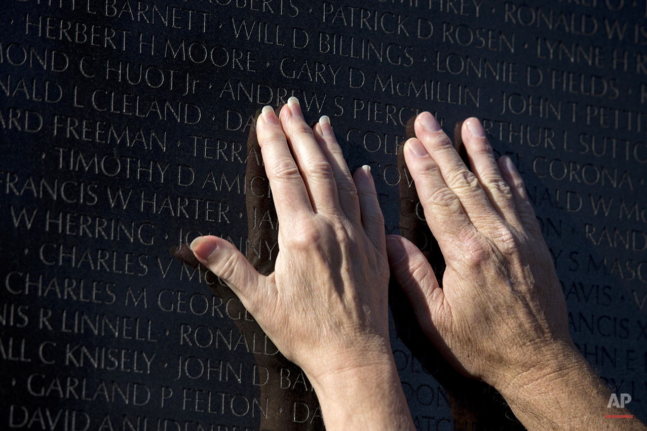 Dan Howieson, right, and his wife Catherine Howieson, from Montgomery, Ala, touch the name of their classmate Darrell Colford, who was killed in Bien Hoa in the province of Dong Nai, Vietnam, inscribed on the Vietnam Veterans Memorial during Veterans Day commemoration in Washington, Tuesday, Nov. 11, 2014. The Howiesons named their son in his honor.   (AP Photo/Manuel Balce Ceneta)