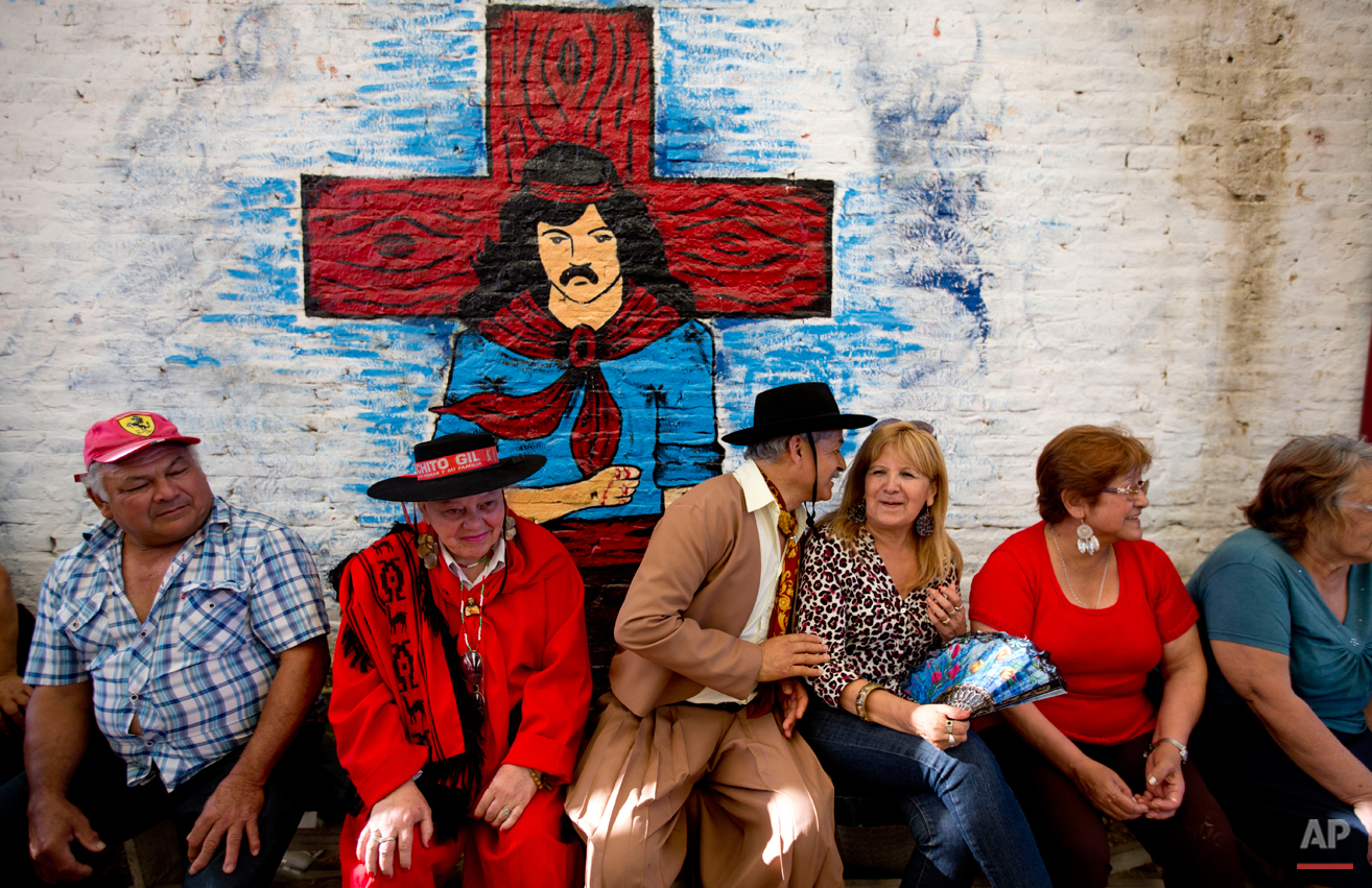 In this Nov. 8, 2014 photo, followers of popular folk saint Gauchito Gil, some dressed like him, gather at a sanctuary built in his honor on the anniversary of his death in Alejandro Korn, Argentina. This sanctuary was built by Ruben Alfaro, who believes Gil cured him of colon cancer. To give thanks, he built this sanctuary where pilgrims come every eighth of the month to pay him tribute. (AP Photo/Natacha Pisarenko)
