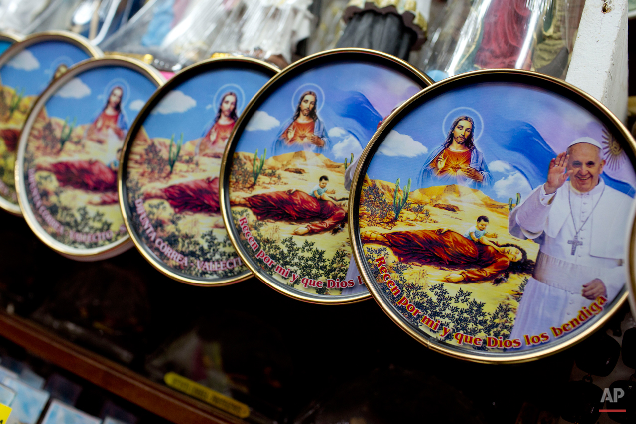 "In this Nov. 2, 2014 photo, souvenirs showing Pope Francis with Jesus Christ and Deolinda Correa, better known as ""La Difunta Correa"" hang on a shelf for sale at her sanctuary in Vallecito in the San Juan province of Argentina. Devotes of Correa say they're Catholic but find no contradiction, even though she's not recognized by the church. According to Daniel Rojas, who runs the sanctuary, the church was asked to make Correa a saint but said since there's no historical documentation, so she will always be considered a legend. (AP Photo/Natacha Pisarenko)"