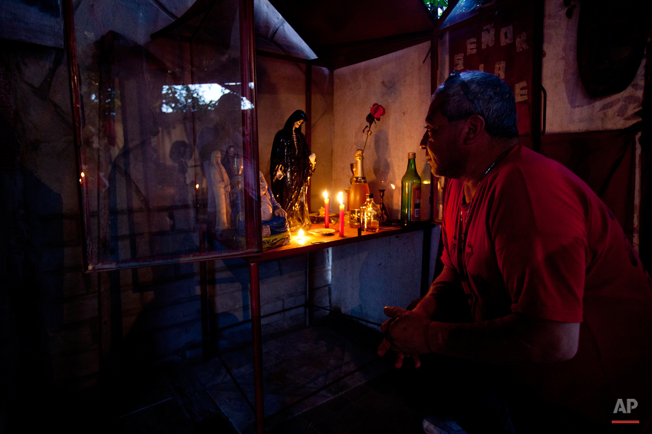 In this Oct. 8, 2014 photo, Carlos Marquez sits in front of his altar in honor of San La Muerte at his home in the La Carcova slum on the outskirts of Buenos Aires, Argentina. Marquez says his devotion to San La Muerte began in prison, where he served 15 years for armed robbery. He built the altar in thanks for being alive, and says many youth in his neighborhood with drug problems and criminal pasts pray at his alter. (AP Photo/Natacha Pisarenko)
