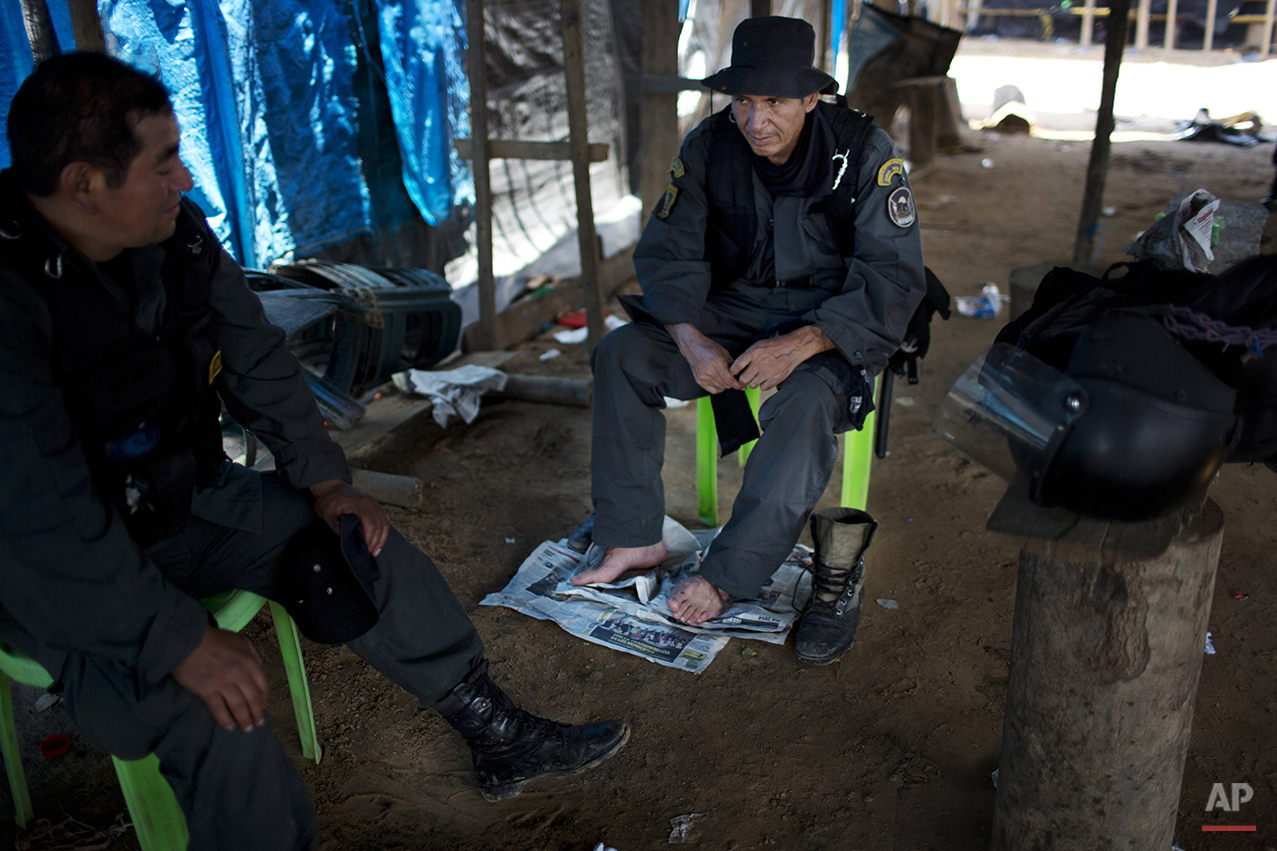 In this Nov. 11, 2014 photo, policemen rest in an illegal gold mining camp they occupied in an operation to eradicate illegal mining in the area known as La Pampa, in Peru's Madre de Dios region. Peru's anti-illegal mining czar, retired army Gen. Augusto Soto, marched his men to the wasteland known as La Pampa, where 50,000 hectares of rainforest have been obliterated in the past six years. In addition to contributing to deforestation, the illegal alluvial gold mining contaminates the jungle with tons of mercury.(AP Photo/Rodrigo Abd)