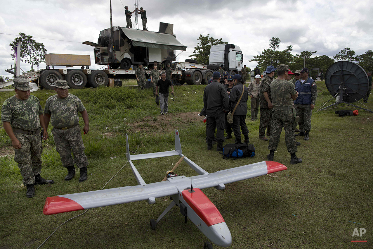 In this Nov. 11, 2014 photo, two soldiers look at a drone, used by the Peruvian Air Force to track illegal mining activity, as they prepare for an operation to eradicate illegal gold mining camps in the area known as La Pampa, in Peru's Madre de Dios region. Less than a month before Peru plays host to global climate talks, the government sent a battalion of police into southeastern jungles to dismantle illegal gold-mining mining camps. Peru's anti-illegal mining czar, retired army Gen. Augusto Soto, marched the men to the wasteland known as La Pampa, where 50,000 hectares of rainforest have been obliterated in the past six years. (AP Photo/Rodrigo Abd)