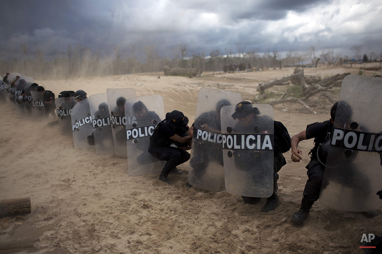 In this Nov. 12, 2014 photo, policemen use their shields to protect themselves from dust clouds stirred by a landing helicopter, after taking part in an operation to eradicate illegal gold mining camps in the area known as La Pampa, in Peru's Madre de Dios region. Less than a month before Peru plays host to global climate talks, the government sent a battalion of police into the southeastern jungles to dismantle illegal gold-mining mining camps. Peru first criminalized unlicensed gold mining in 2012 but only began enforcing the law vigorously this year with serious manpower and explosives. (AP Photo/Rodrigo Abd)