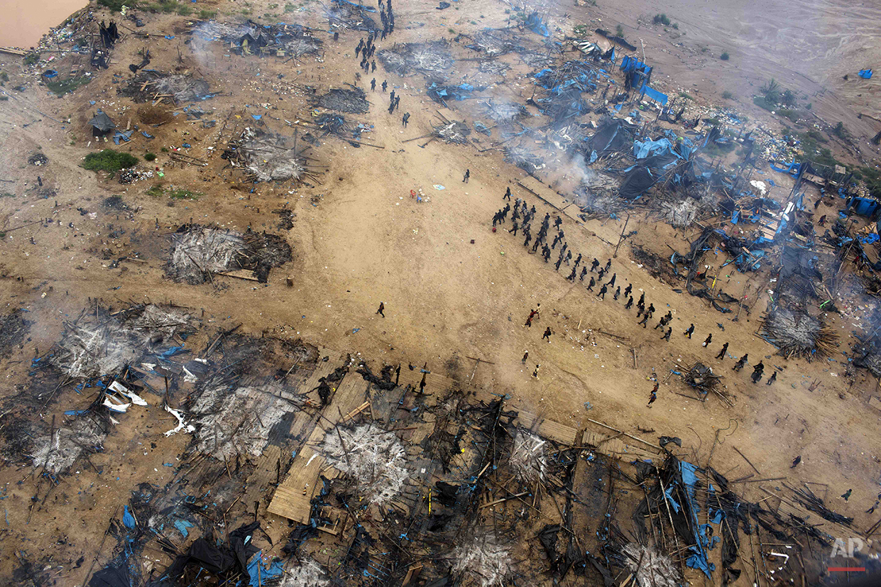 In this Nov. 12, 2014 photo, a column of policemen occupy a gold mining camp as part of an operation to eradicate illegal mining in the area  known as La Pampa, in Peru's Madre de Dios region. Less than a month before Peru plays host to global climate talks, the government sent a battalion of police into southeastern jungles to dismantle illegal gold-mining mining camps. Peru's anti-illegal mining czar, retired army Gen. Augusto Soto, marched the men to the wasteland known as La Pampa, where 50,000 hectares of rainforest have been obliterated in the past six years. (AP Photo/Rodrigo Abd)