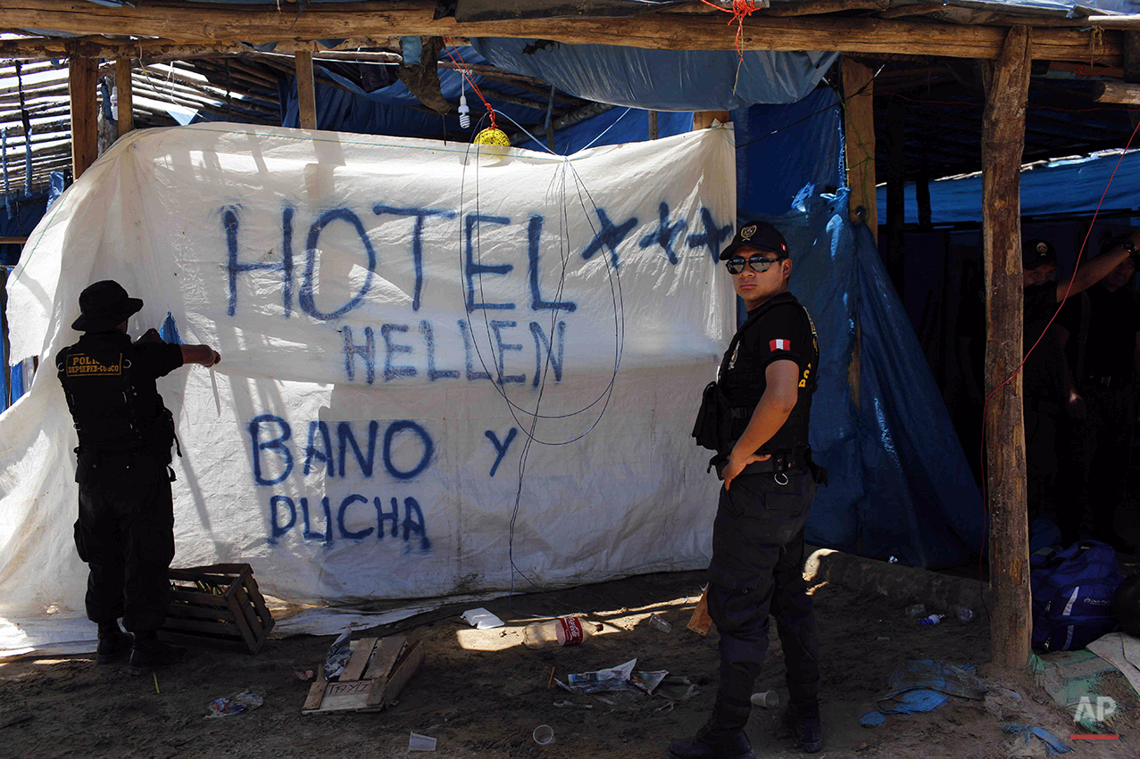 """In this Nov. 11, 2014 photo, a policeman begins to rip apart a tarp advertising restroom and shower services for the """"Hotel Hellen,"""" set up in an illegal gold mining camp, occupied in an operation to eradicate illegal mining in the area known as La Pampa, in Peru's Madre de Dios region. Less than a month before Peru plays host to global climate talks, the government sent a battalion police into southeastern jungles to dismantle illegal gold-mining mining camps. Police destroyed motors and dynamited a dozen motorcycles as they tore down dwellings that included at least one mud-flanked bordello. (AP Photo/Rodrigo Abd)"""