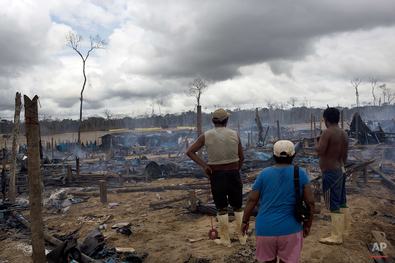 In this Nov. 12, 2014 photo, small scale gold miners stand looking at the remains of their mining camp, scorched by authorities as part of an operation to eradicate illegal gold mining camps in the area known as La Pampa, in Peru's Madre de Dios region. Less than a month before Peru plays host to global climate talks, the government sent a battalion of police into southeastern jungles to dismantle illegal gold-mining mining camps. Peru first criminalized unlicensed gold mining in 2012 but only began enforcing the law vigorously this year with serious manpower and explosives. The operations have displaced thousands of the estimated 40,000 people who authorities say moved to the jungle to mine gold. (AP Photo/Rodrigo Abd)