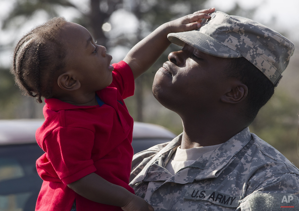 National Guard soldier Carlos Clopton holds his son Caleb, 11-months, following a deployment ceremony at the Fort Deposit Municipal Complex in Fort Deposit, Ala., Wednesday, Feb. 15, 2012.  Almost 120 members of the 781st Transportation Company are being deployed to provide transportation to other military groups throughout the region.  (AP Photo/Dave Martin)
