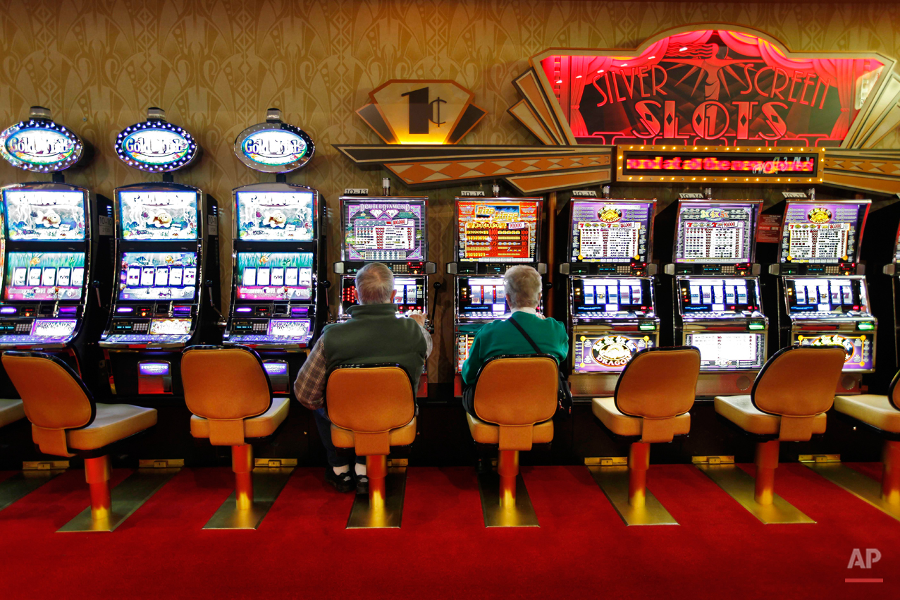 In this March 16, 2012 photo, a couple plays the slot machines at Hollywood Slots, Friday, in Bangor, Maine. The Legislature is considering bills to expand gambling operations in Maine for the Passamaquoddy tribe, veterans organizations and other groups. (AP Photo/Robert F. Bukaty)