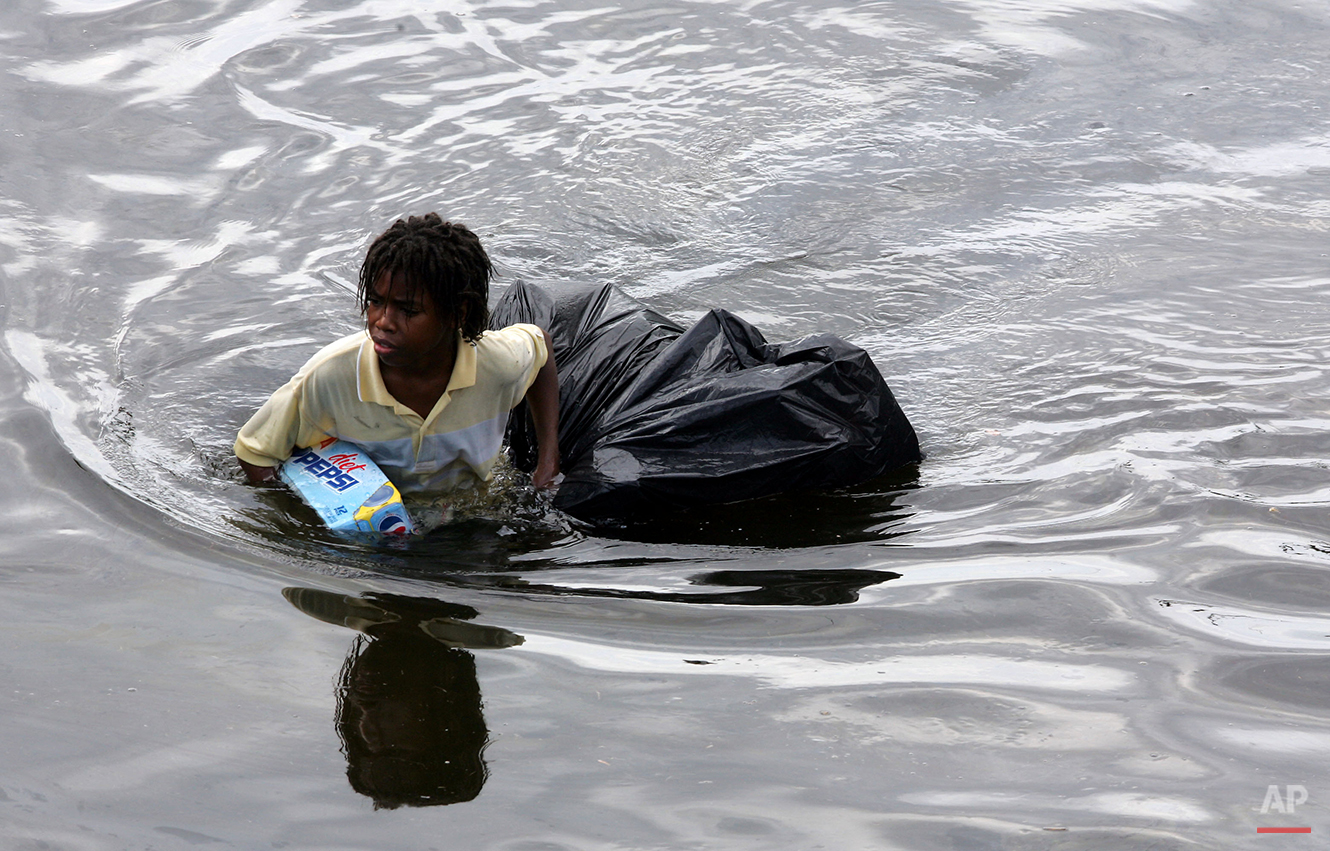 A young man walks through chest deep flood water after looting a grocery store in New Orleans on Tuesday, Aug. 30, 2005.  Flood waters continue to rise in New Orleans after Hurricane Katrina did extensive damage when it made landfall on Monday. (AP Photo/Dave Martin)
