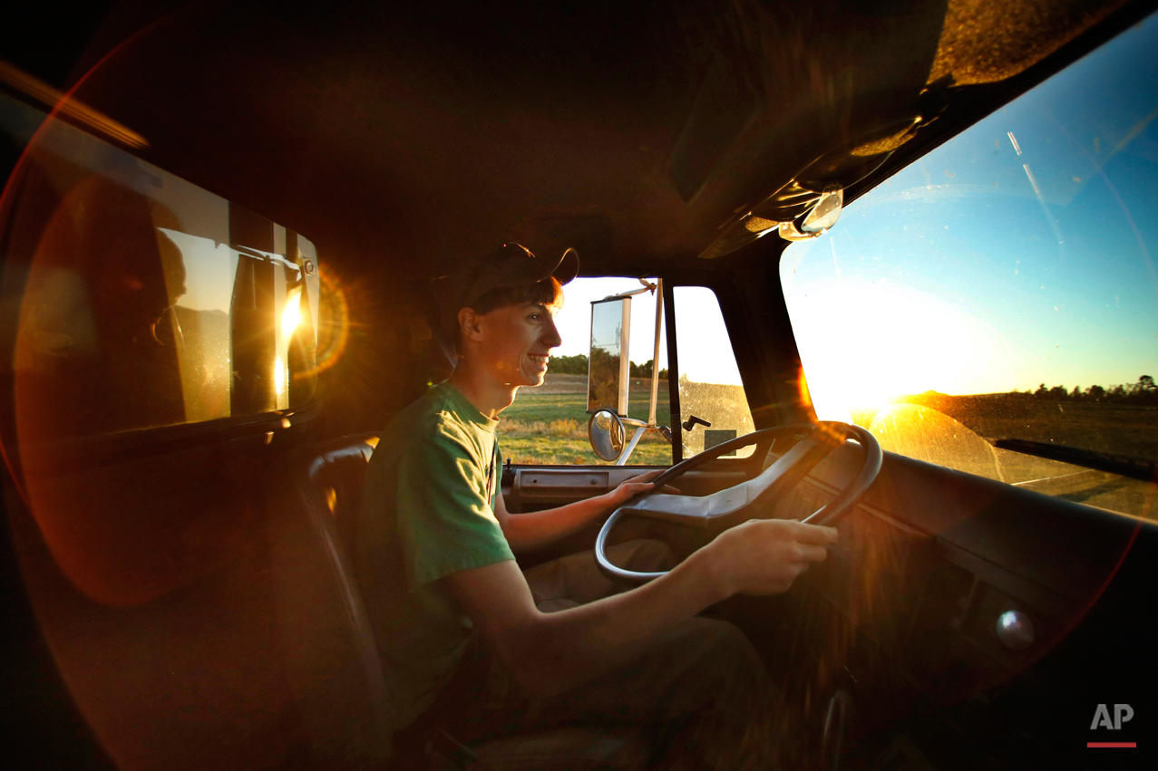 In this photo made Wednesday, Sept. 24, 2014, Nick Powers, 16, drives a 60,000-pound load of potatoes from a field to a storage facility in Mapleton, Maine. Powers is a junior at Presque Isle High School, one of a half-dozen schools that close for up to three weeks each autumn as kids help to bring in the potato crop. Educators and farmers are clinging to a tradition that give farmers much-needed help and puts money in the pockets of teenagers. (AP Photo/Robert F. Bukaty)