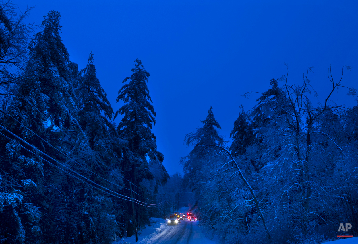 Utility crews prepare to work on power lines at dusk on Thursday, Dec. 26, 2013 in Litchfield, Maine, where many have been without electricity since Monday's ice storm. (AP Photo/Robert F. Bukaty)