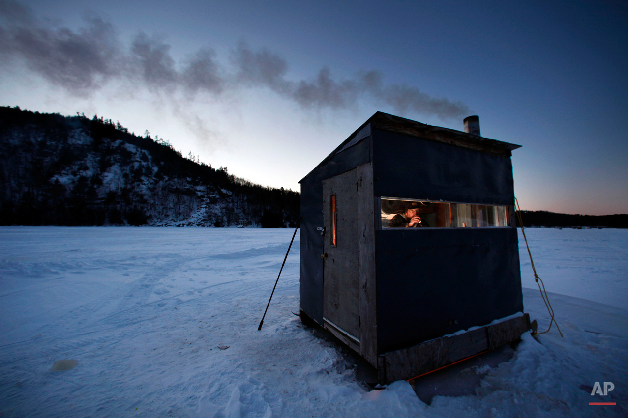 """Tom Locklin, of Bethel, Maine, sips a beer as he looks out of his warm ice fishing shack on Christopher Lake where the temperature was 0 degrees at dusk, Thursday, Jan. 15, 2009, in Bryant Pond, Maine.  """"This weather ain't bad"""" said Locklin, """"but if the wind was really blowing it would be brutal."""" (AP Photo/Robert F. Bukaty)"""