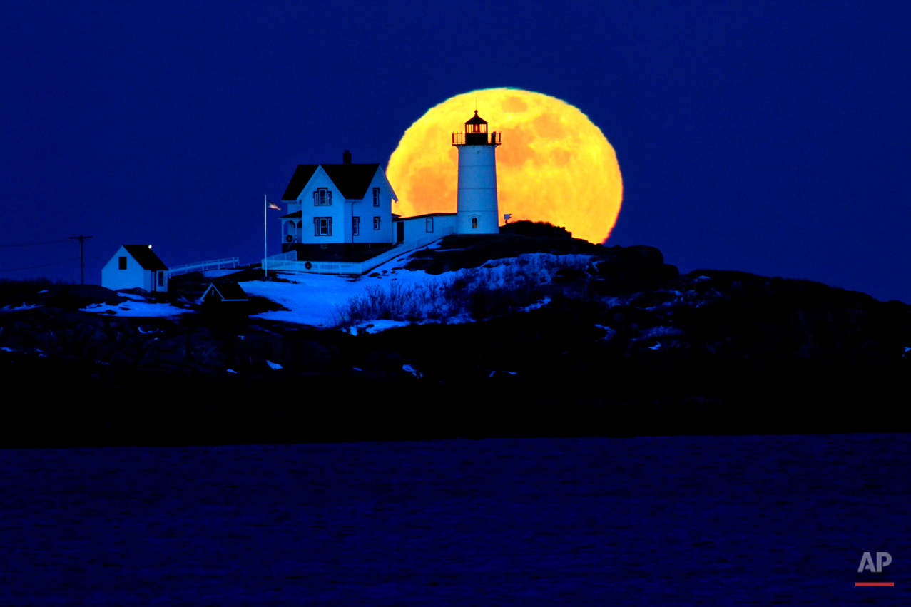 The full moon rises behind Cape Neddick Light, also known as Nubble Light, Feb. 9, 2009, in York, Maine. The February full moon is known as the snow moon. (AP Photo/Robert F. Bukaty)