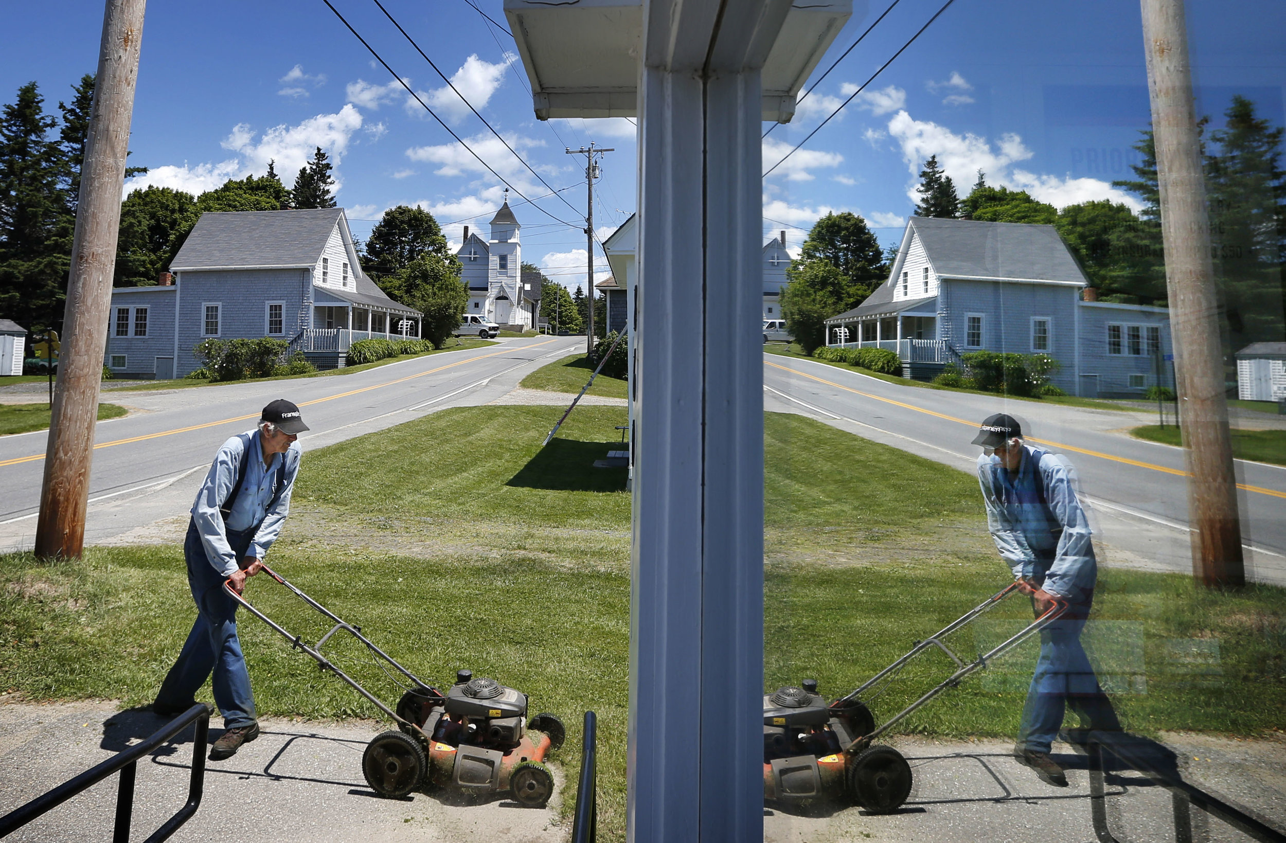 Ralph Russell, 76, is reflected in the front window of the post office, Thursday, June 19, 2014, in Port Clyde, Maine, where he has been cutting the lawn for almost 40 years. (AP Photo/Robert F. Bukaty)
