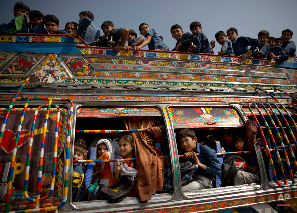 In this Friday, Oct. 4, 2013 photo, Pakistani children crowd on a bus after being picked up from school in Wajah Khiel, Swat Valley, Pakistan. Malala Yousafzai's struggle for girls to be educated in a deeply conservative society led to her shooting by the Taliban two years ago, while her relentless campaign for women's was rewarded Friday, Oct. 10, 2014, by the recognition of her work as she was jointly awarded the Nobel Peace Prize. (AP Photo/Anja Niedringhaus)