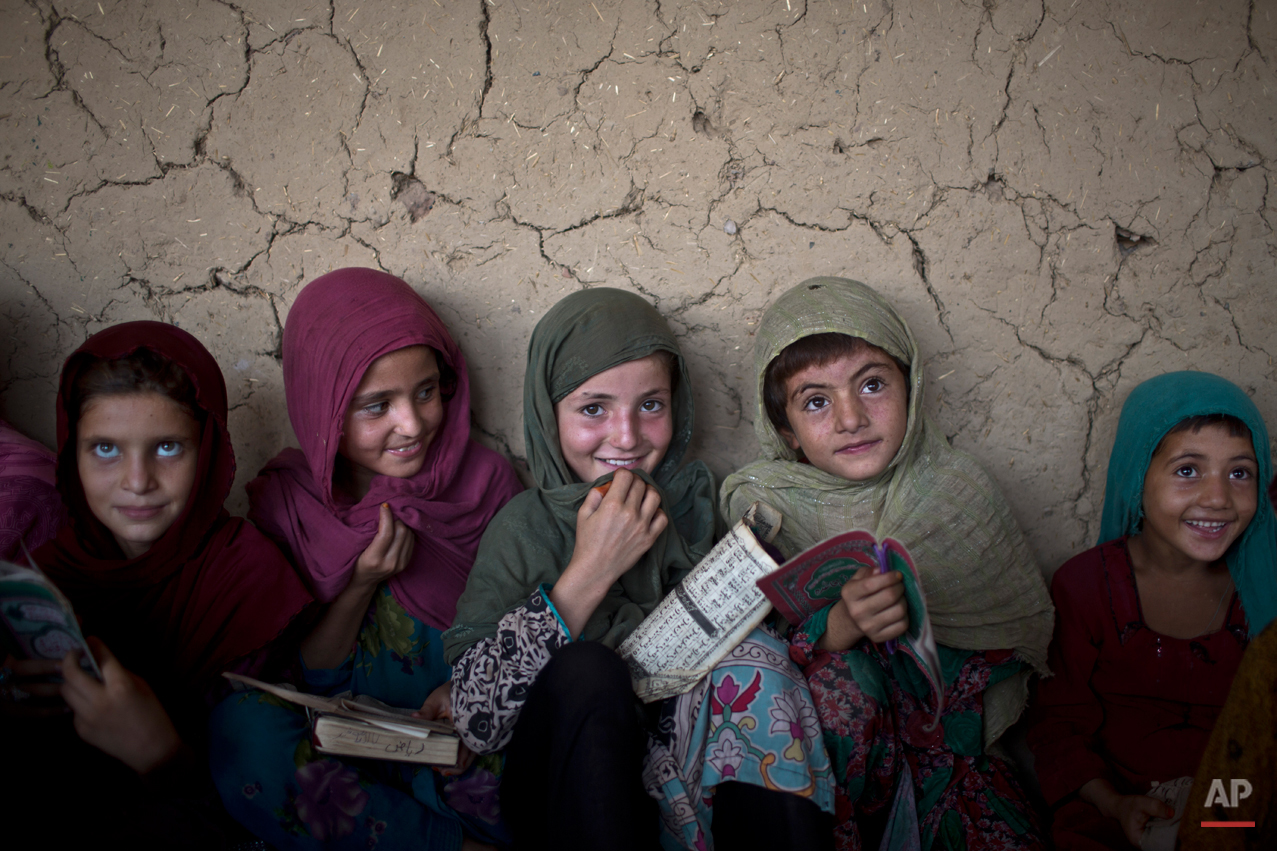 In this Monday, Aug. 11, 2014, photo, Afghan refugee girls listen to their teacher during their daily Madrassa, or Islamic school, at a mosque on the outskirts of Islamabad, Pakistan. Taliban attack survivor Malala Yousafzai of Pakistan won the Nobel Peace Prize on Friday, Oct. 10, 2014, for risking their lives to fight for children's rights. Malala, who moved to Britain for treatment and later settled there, tirelessly continued her campaign for a woman's right to an education in Pakistan and won international recognition for her struggle. But in Pakistan that effort has not stopped as young girls and women struggle to get an education. (AP Photo/Muhammed Muheisen)