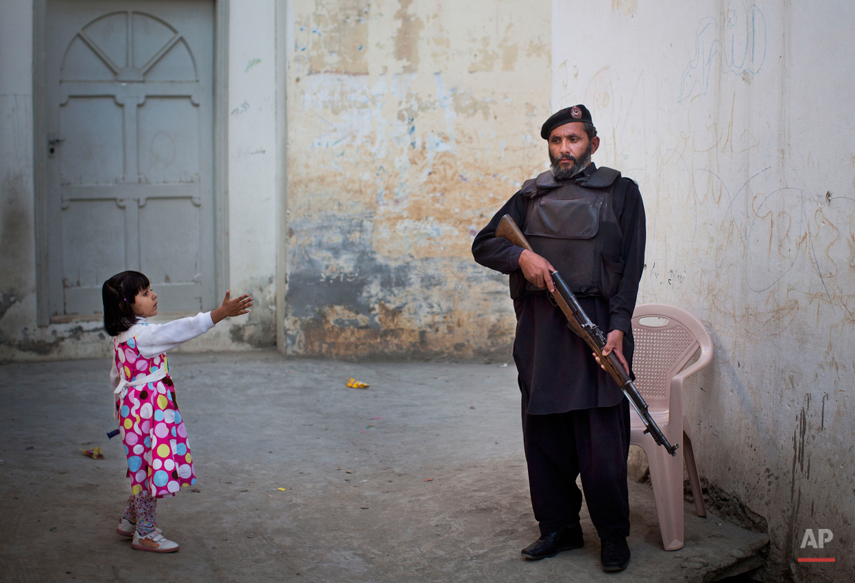 In this Wednesday, Nov. 15, 2012 photo, a young girl in her colorful dress reaches out to greet a Pakistani policeman securing the road outside Kainat Riaz's home in Mingora, Swat Valley, Pakistan. Malala Yousafzai's struggle for girls to be educated in a deeply conservative society led to her shooting by the Taliban two years ago, while her relentless campaign for women's rights was rewarded Friday, Oct. 10, 2014, by the recognition of her work as she was jointly awarded the Nobel Peace Prize. ( AP Photo/Anja Niedringhaus)