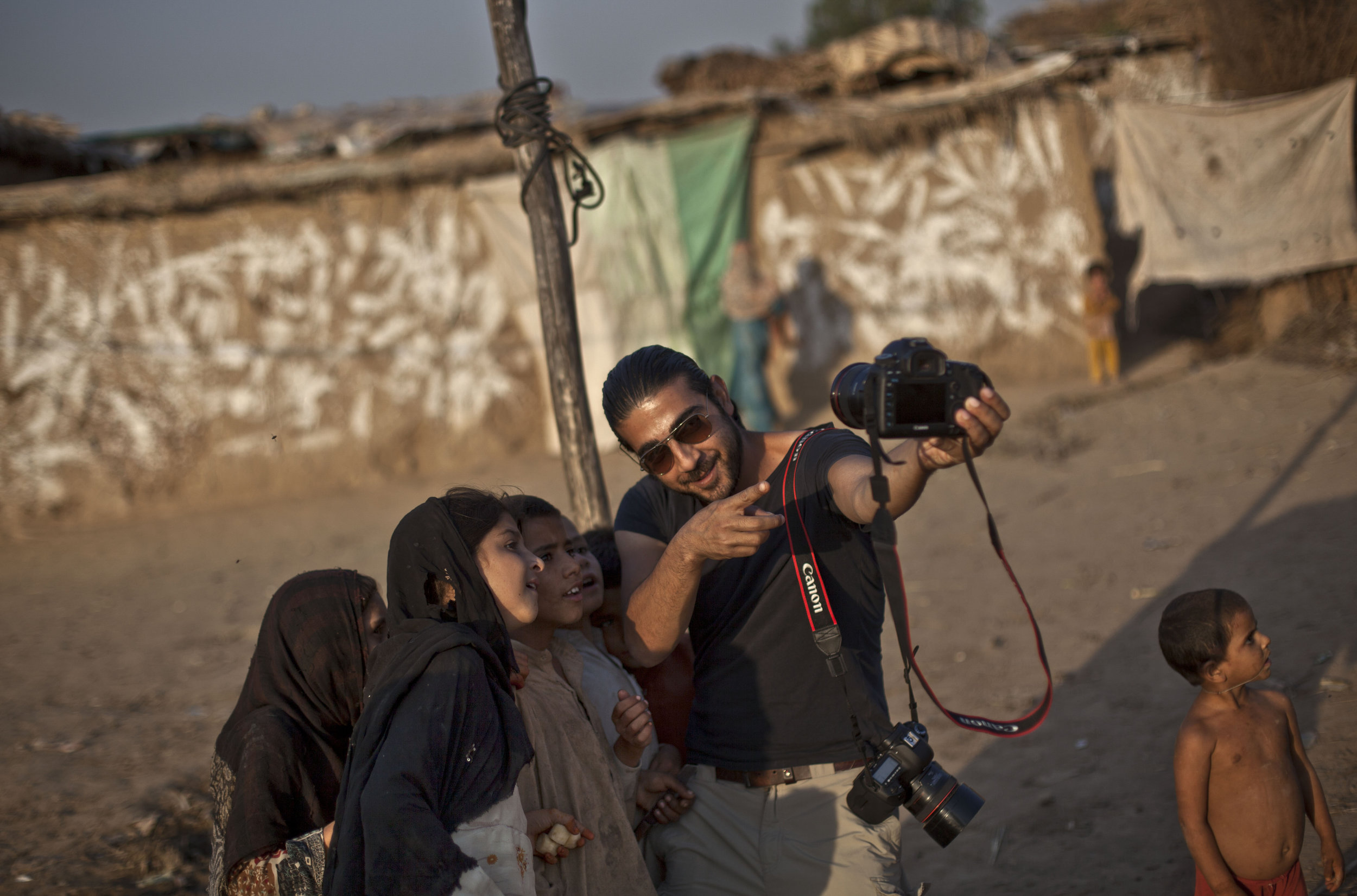 Pakistan's Chief Photographer Muhammed Muheisen shows Afghan refugee children how the camera works, in a poor neighborhood on the outskirts of Islamabad, Pakistan, Monday, Oct. 21, 2013. (AP Photo/Nathalie Bardou)