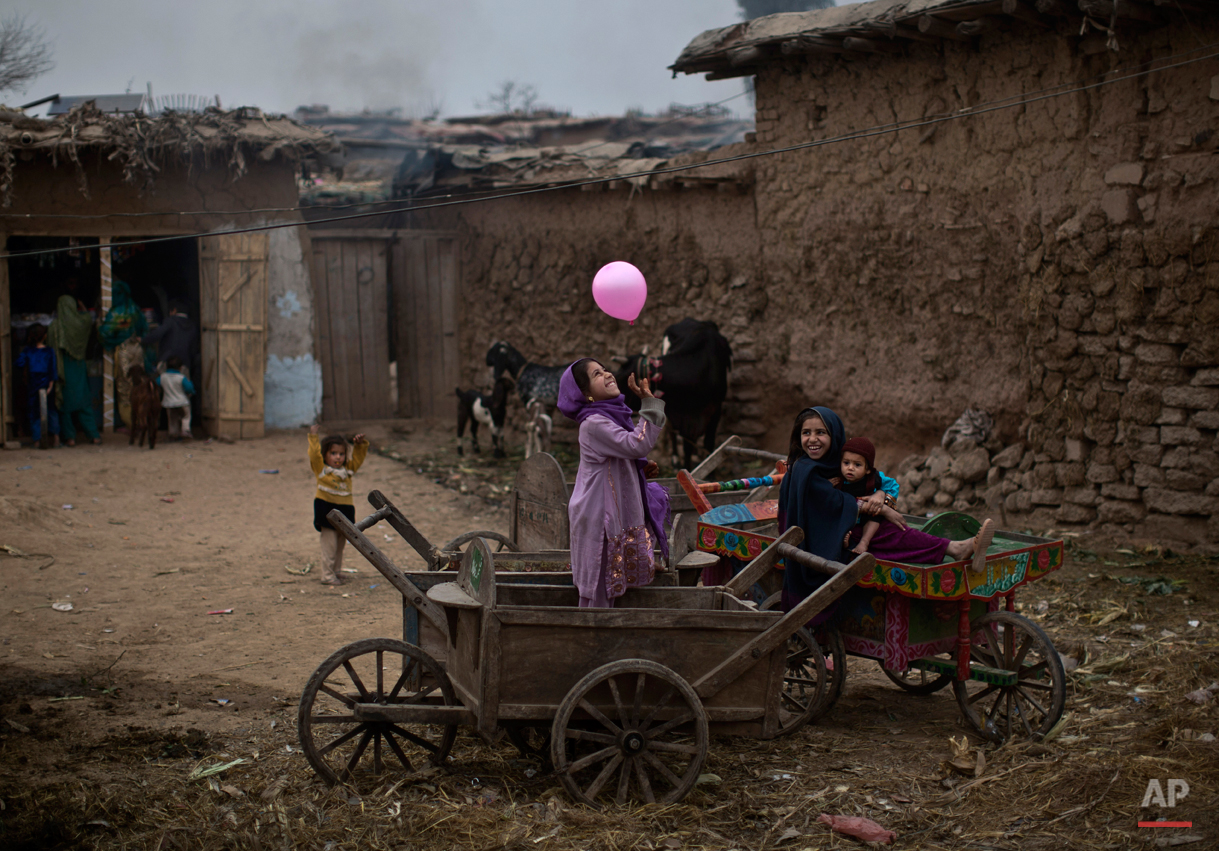 An Afghan refugee girl, right, holding her younger brother, sits on a wooden-cart looking at her friend playing with a balloon, in a poor neighborhood on the outskirts of Islamabad, Pakistan, Sunday, Feb. 2, 2014. (AP Photo/Muhammed Muheisen)