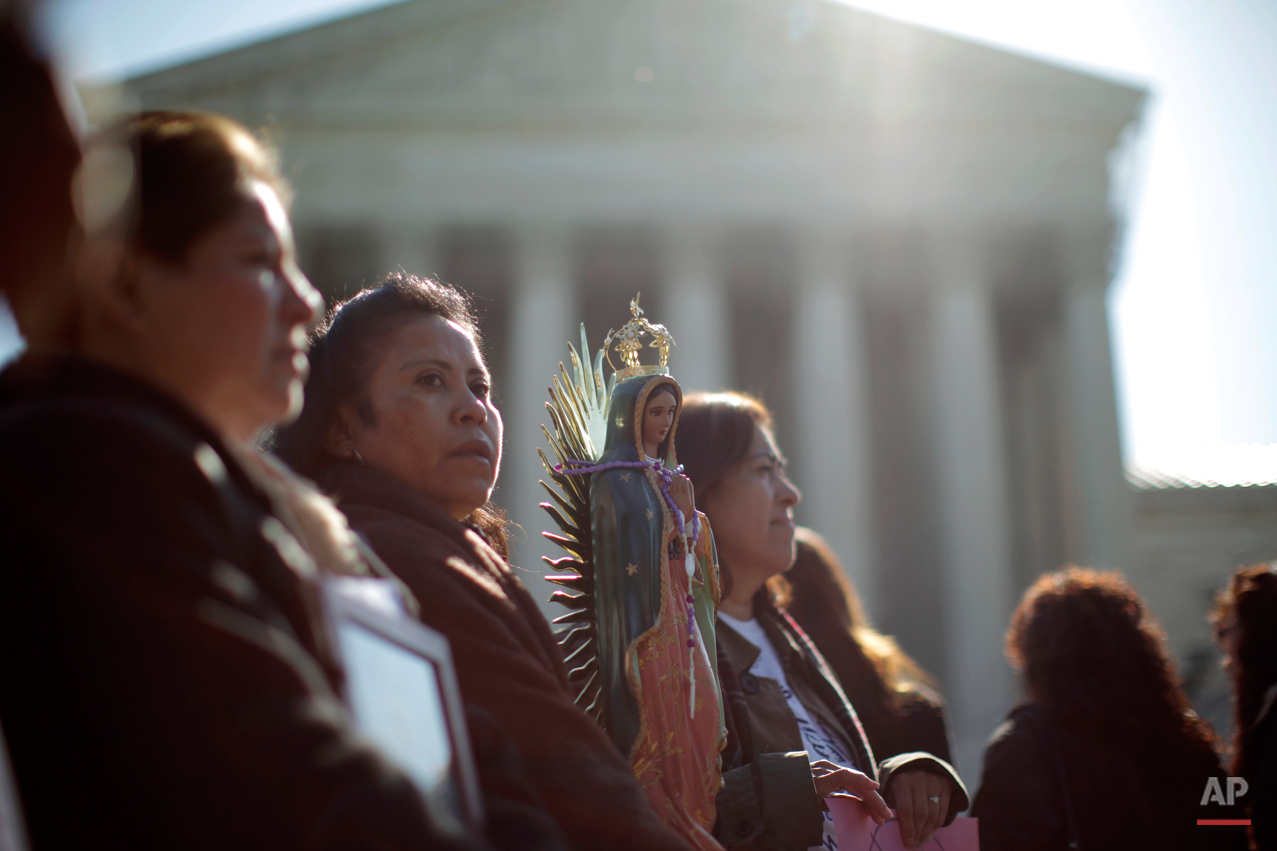 "Leonida Martinez, from Phoenix, Ariz., second from left, and others take part in a demonstration in front of the Supreme Court in Washington, Wednesday, April 25, 2012, as the court questions Arizona's ""show me your papers"" immigration law. (AP Photo/Charles Dharapak)"