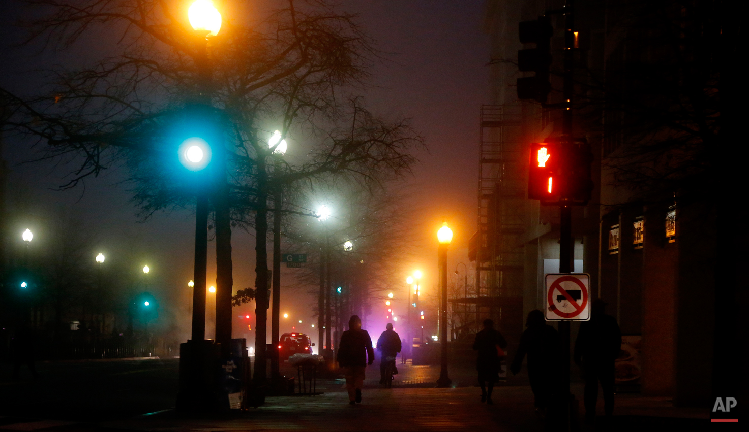 Pedestrians walk in a morning fog on 17th Street and Pennsylvania Avenue NW across from the Eisenhower Executive Office Building in Washington, Wednesday, Jan. 15, 2014. A dense fog has caused limited visibility in the Washington area. (AP Photo/Charles Dharapak)
