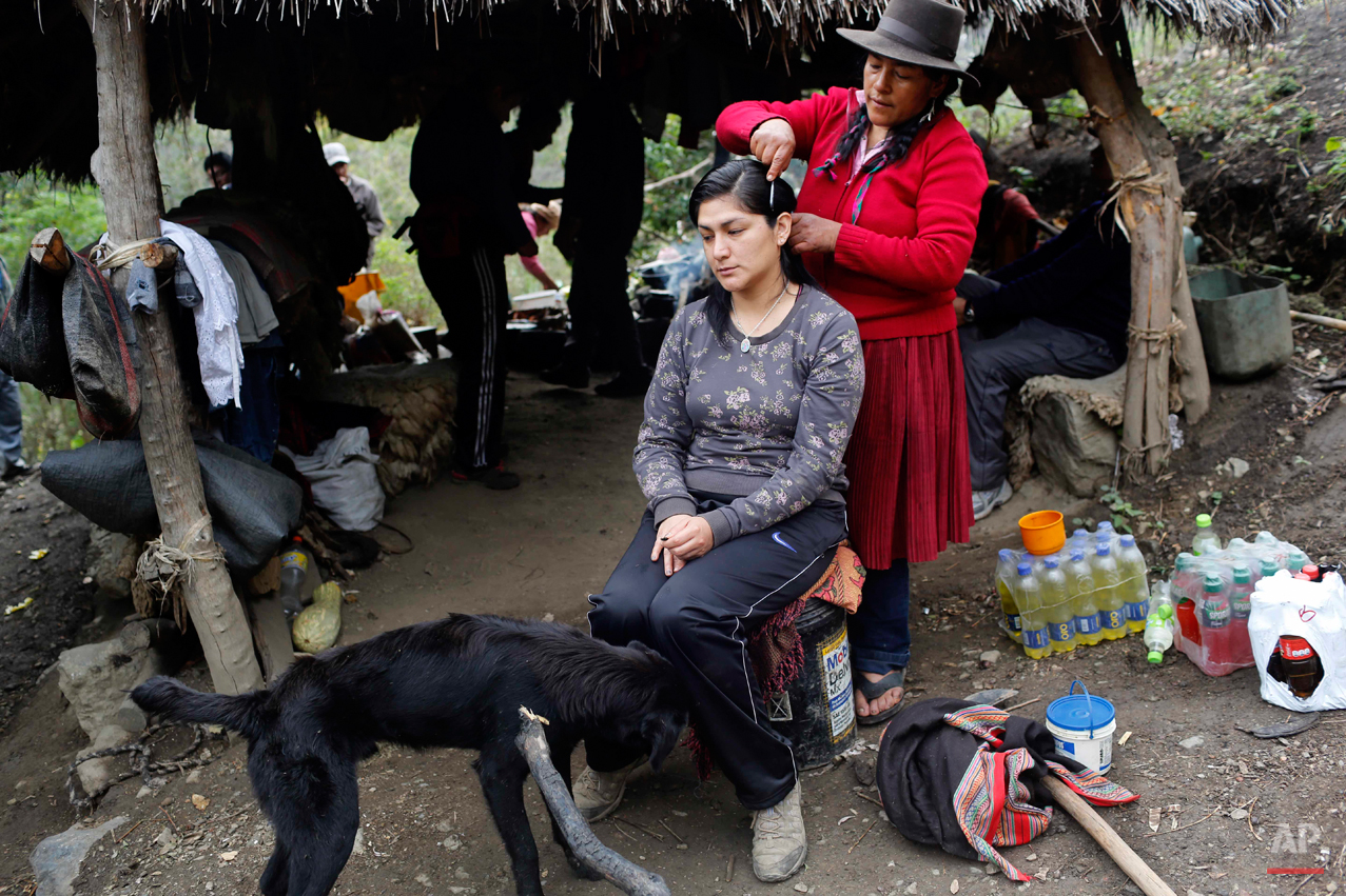 In this Sept. 6, 2014 photo, Dolores Guzman combs archeologist Soledad Mostacero's hair in the Paccha village of Peru. Guzman, sole survivor of a 1984 massacre in Paccha, set aside the street stand where she sells hard-boiled eggs in Lima and journeyed to the Paccha to help forensic investigators find the common graves with the bodies of villagers slain by security forces who considered those slain adherents of the Shining Path rebels. (AP Photo/Rodrigo Abd)