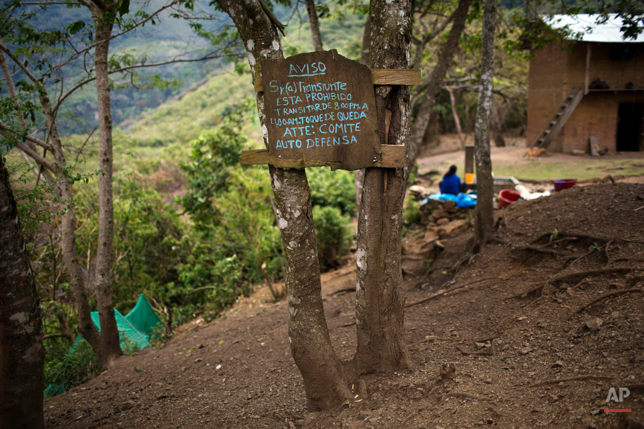 "In this Sept. 9, 2014 photo, a warning sign nailed to trees and posted by the local Civil Defense Committee reads in Spanish, ""It is forbidden to be out between 8:00PM. and 4:00 A.M. due to a curfew,"" in the Torre village, Peru. This rugged southeastern region known as ìOreja de Perro,î or Dogís Ear, lacks telephones, super markets and good roads. Cocaine-trafficking remnants of the otherwise conquered Shining Path movement coexist here with young Quechua men who ferry coca paste over the Andes in backpacks. (AP Photo/Rodrigo Abd)"