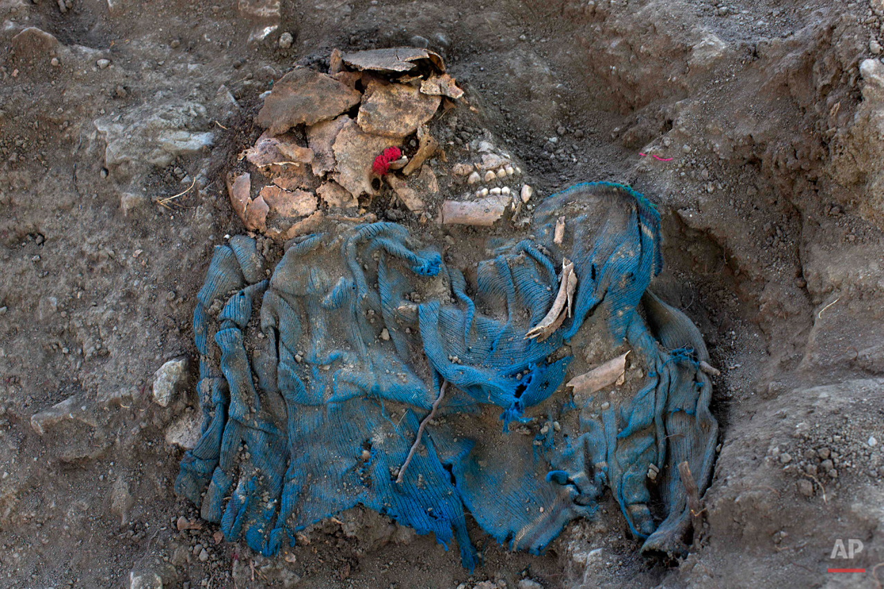In this Sept. 7, 2014 photo, the remains of an unidentified villager lies unearthed from a common grave, exhumed by forensic anthropologists in the Paccha village of Peru. Forensic investigators began unearthing the remains of the nearly two dozen victims of the July 14, 1984 massacre in this region where government forces regularly hunted alleged collaborators of the Maoist guerrillas. (AP Photo/Rodrigo Abd)