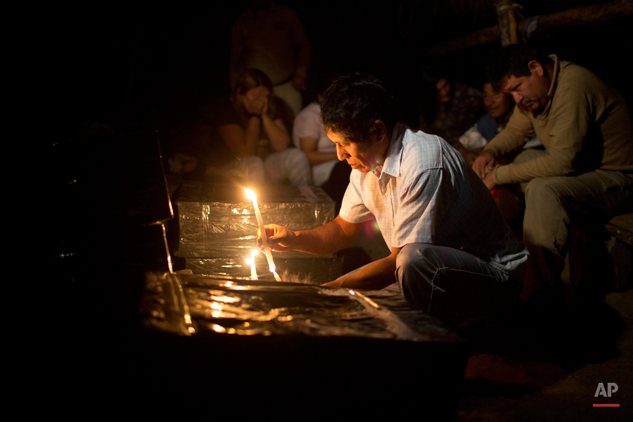 In this Sept. 8, 2014 photo, Cipriano Huaman, who recognized his brother's clothes in an unearthed mass grave, lights a candle during a vigil for remains exhumed by forensic anthropologists in the Peruvian village of Paccha. Forensic investigators began unearthing the remains of the nearly two dozen victims of the July 14, 1984 massacre in Paccha, a village located in a region where government forces regularly hunted alleged collaborators of the Maoist guerrillas during the 1980-2000 internal conflict. (AP Photo/Rodrigo Abd)