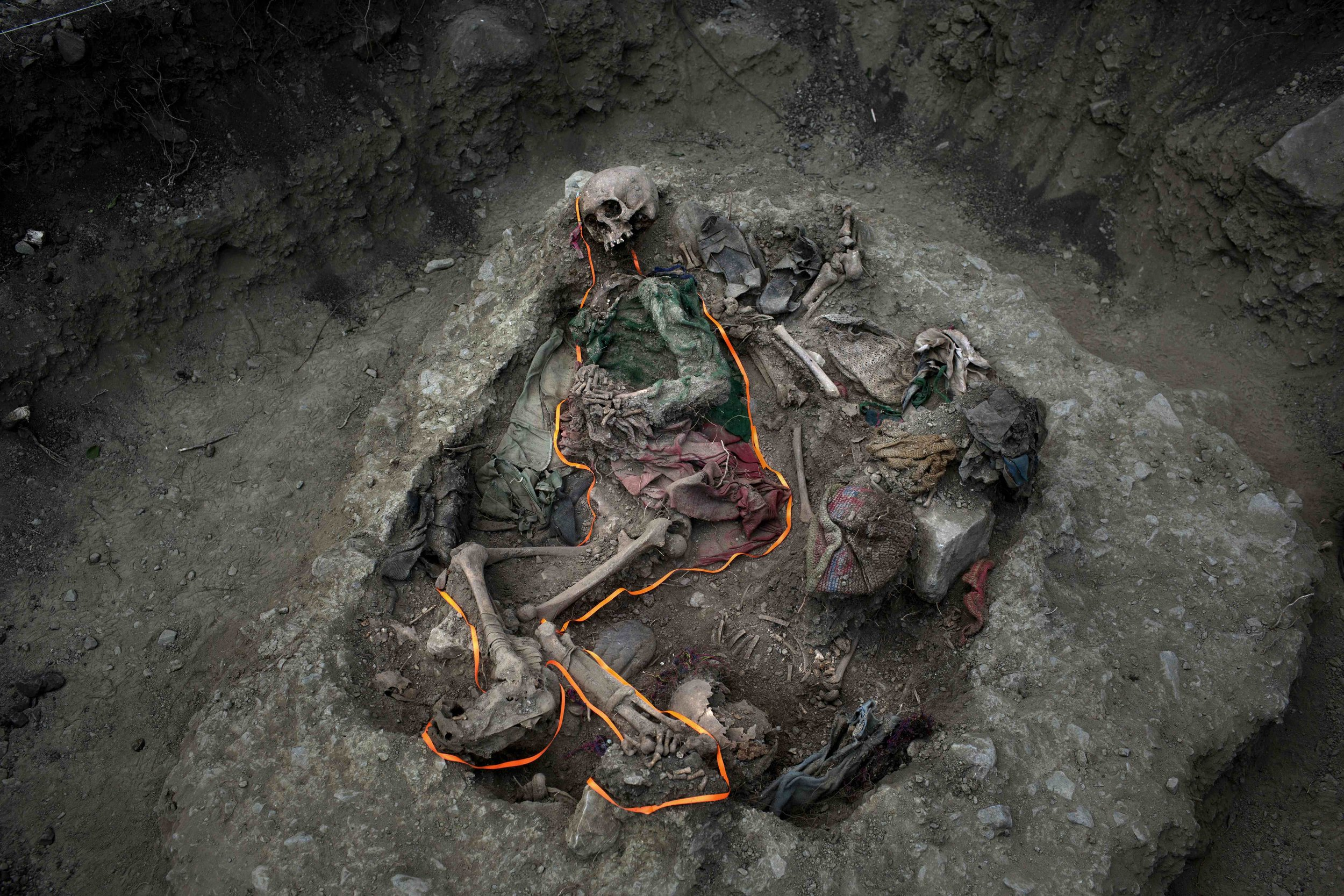 In this Sept. 8, 2014 photo, an orange ribbon outlines skeletal remains in a mass grave, unearthed in the village Paccha of Peru. For three decades, the soil of this unpopulated hamlet on the Andean slopes beside the Apurimac river guarded bodies of villagers slain by security forces who considered them adherents of the Shining Path rebels. (AP Photo/Rodrigo Abd)