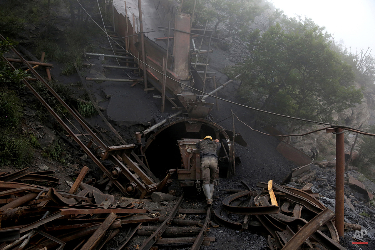 In this Thursday, May 8, 2014 photo, an Iranian coal miner pushes an old metal cart to be loaded with coal at a mine near the city of Zirab 212 kilometers (132 miles) northeast of the capital Tehran on a mountain in Mazandaran province, Iran. A miner said they move up to 100 tons a day. (AP Photo/Ebrahim Noroozi)