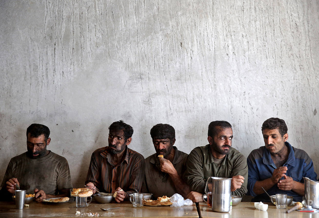 In this Tuesday, Aug. 19, 2014 photo, Iranian coal miners eat lunch at a mine near the city of Zirab 212 kilometers (132 miles) northeast of the capital Tehran, on a mountain in Mazandaran province, Iran. International sanctions linked to the decade-long dispute over Iran's nuclear program have hindered the import of heavy machinery and modern technology in all sectors, and coal mining is no exception. The decision to privatize the industry 10 years ago has further squeezed miners, who work often in dangerous conditions -- and make just $300 a month, little more than minimum wage. (AP Photo/Ebrahim Noroozi)