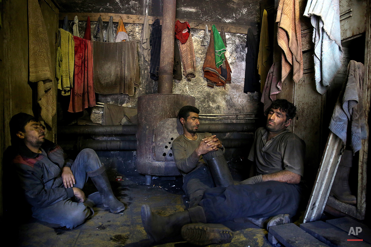 In this Tuesday, May 6, 2014 photo, Iranian coal miners rest during a break at a mine on a mountain in Mazandaran province, near the city of Zirab, 212 kilometers (132 miles) northeast of the capital Tehran, Iran. The miners put in long hours in often dangerous conditions and make just $300 a month, little more than minimum wage. (AP Photo/Ebrahim Noroozi)