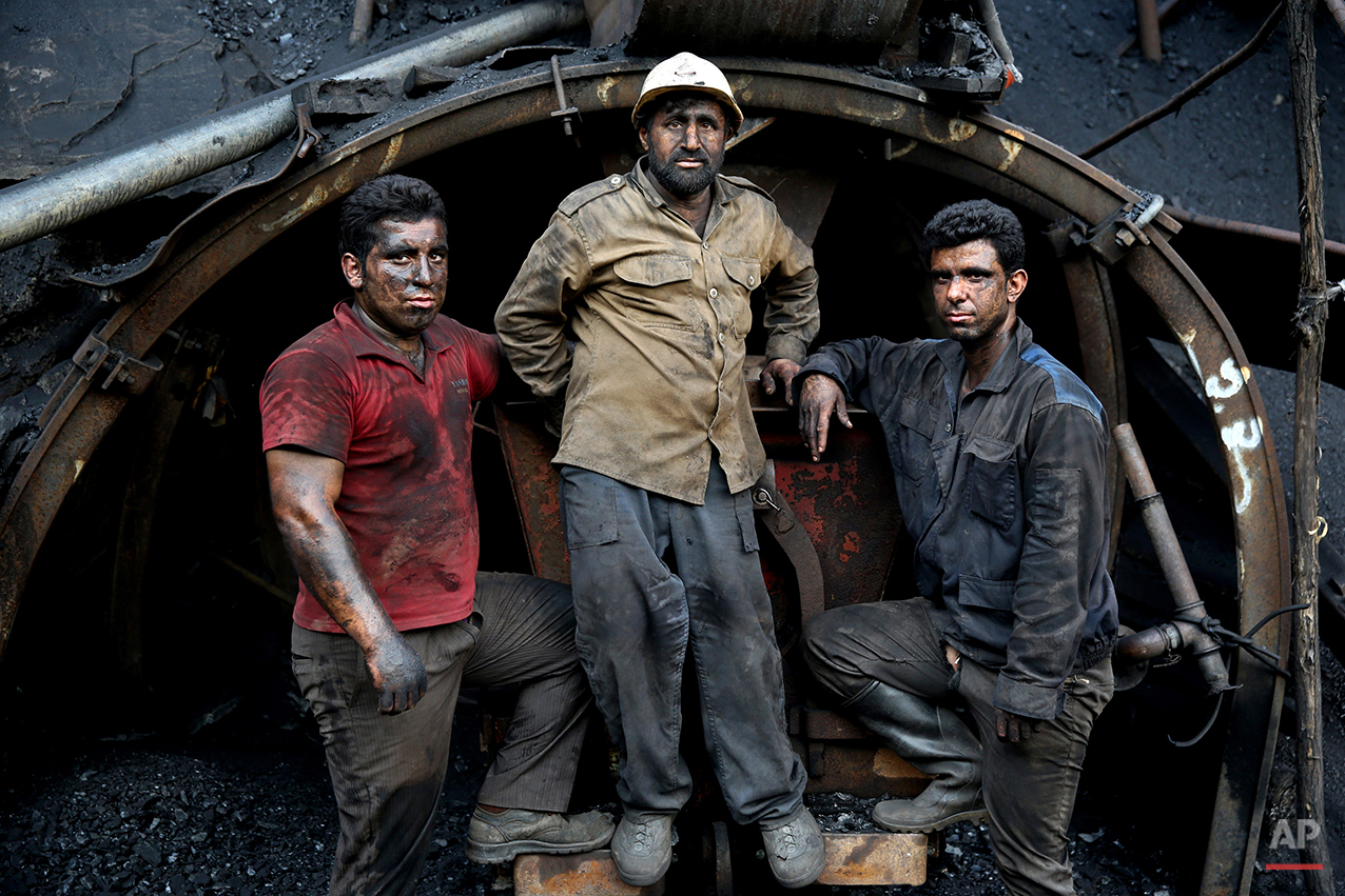In this Monday, Aug. 18, 2014 photo, Iranian coal miners pose for a photograph at a mine on a mountain in Mazandaran province, near the city of Zirab 212 kilometers (132 miles) northeast of the capital Tehran, Iran. International sanctions linked to the decade-long dispute over Iran's nuclear program have hindered the import of heavy machinery and modern technology in all sectors, and coal mining is no exception. The decision to privatize the industry 10 years ago has further squeezed miners, who work often in dangerous conditions -- and make just $300 a month. (AP Photo/Ebrahim Noroozi)