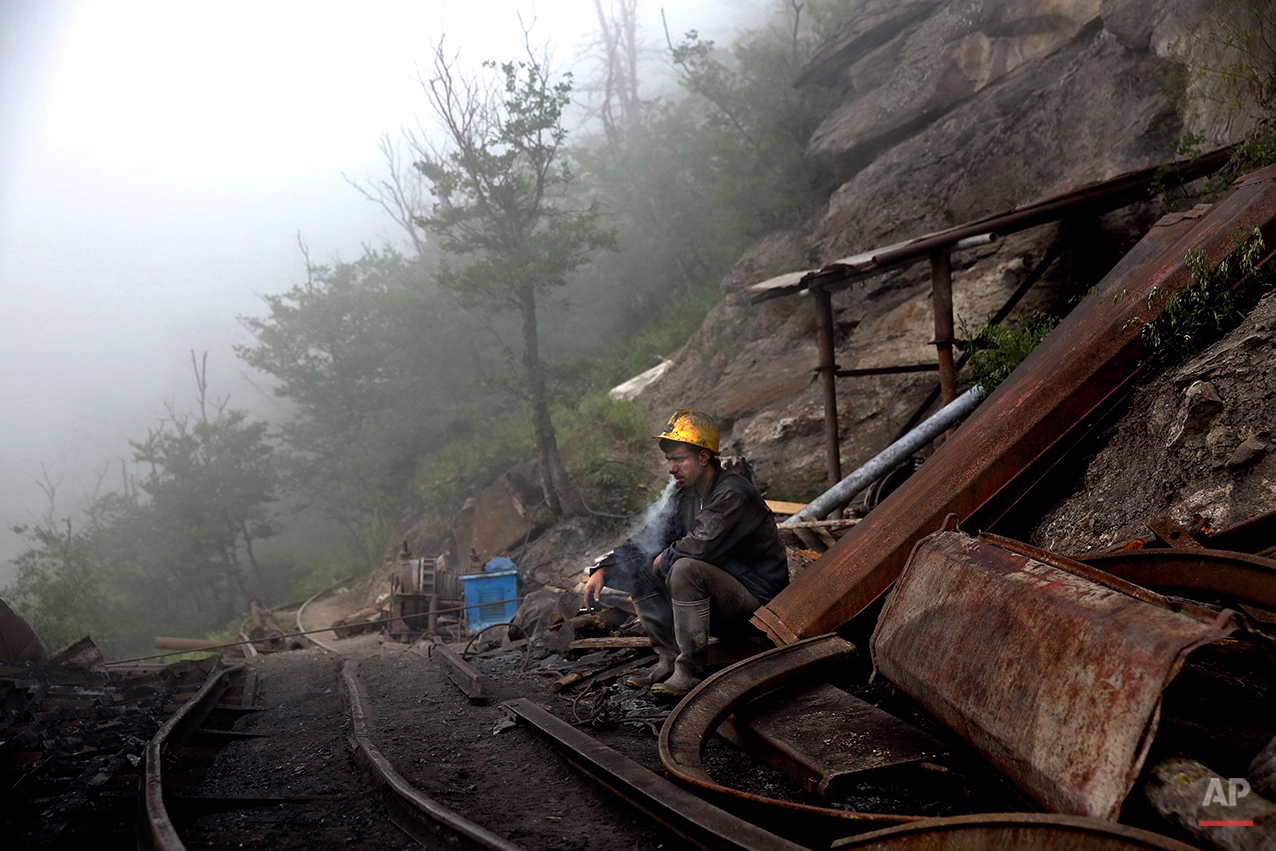 In this Thursday, May 8, 2014 photo, an Iranian coal miner takes a break at a mine near the city of Zirab 212 kilometers (132 miles) northeast of the capital Tehran, on a mountain in Mazandaran province, Iran.  International sanctions linked to the decade-long dispute over Iran's nuclear program have hindered the import of heavy machinery and modern technology in all sectors, and coal mining is no exception. The decision to privatize the industry 10 years ago has further squeezed miners, who work often in dangerous conditions -- and make just $300 a month, little more than minimum wage. (AP Photo/Ebrahim Noroozi)