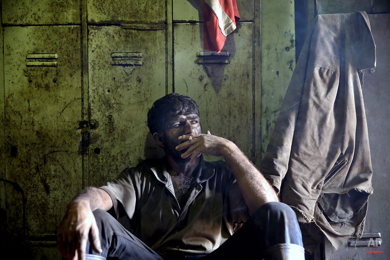 In this Tuesday, Aug. 19, 2014 photo, an Iranian coal miner smokes a cigarette during a break at a mine on a mountain in Mazandaran province, near the city of Zirab 212 kilometers (132 miles) northeast of the capital Tehran, Iran. International sanctions linked to the decade-long dispute over Iran's nuclear program have hindered the import of heavy machinery and modern technology in all sectors, and coal mining is no exception. The decision to privatize the industry 10 years ago has further squeezed miners, who work often in dangerous conditions -- and make just $300 a month. (AP Photo/Ebrahim Noroozi)