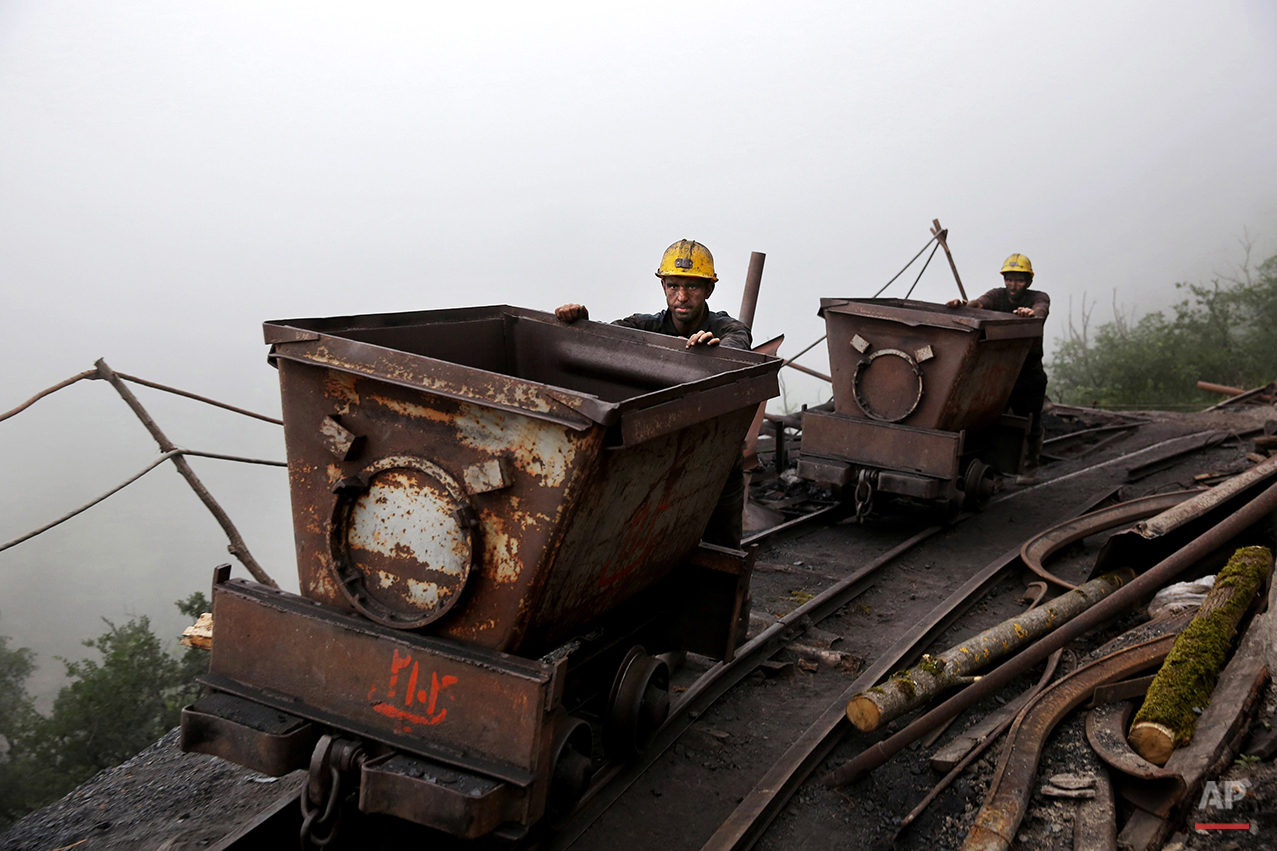 In this Thursday, May 8, 2014 photo, Iranian coal miners push metal carts to be loaded with coal at a mine near the city of Zirab 212 kilometers (132 miles) northeast of the capital Tehran, on a mountain in Mazandaran province, Iran. International sanctions linked to the decade-long dispute over Iran's nuclear program have hindered the import of heavy machinery and modern technology in all sectors, and coal mining is no exception. (AP Photo/Ebrahim Noroozi)