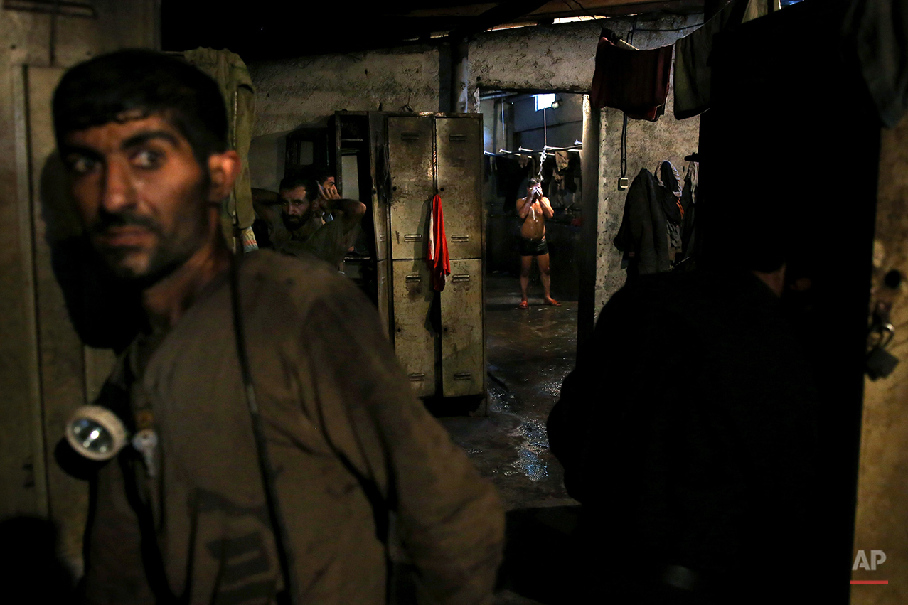 In this Tuesday, May 6, 2014 photo, an Iranian coal miner takes a shower while others prepare to go home after a long day of work at a mine on a mountain in Mazandaran province, near the city of Zirab, 212 kilometers (132 miles) northeast of the capital Tehran Iran. Around 1,200 miners work across 10 mines in the Mazandaran province, in a mountainous, verdant area. More than 12,000 tons of coal is extracted from the mines each month, almost all of which is shipped south for use in Iran's steel industry. (AP Photo/Ebrahim Noroozi)