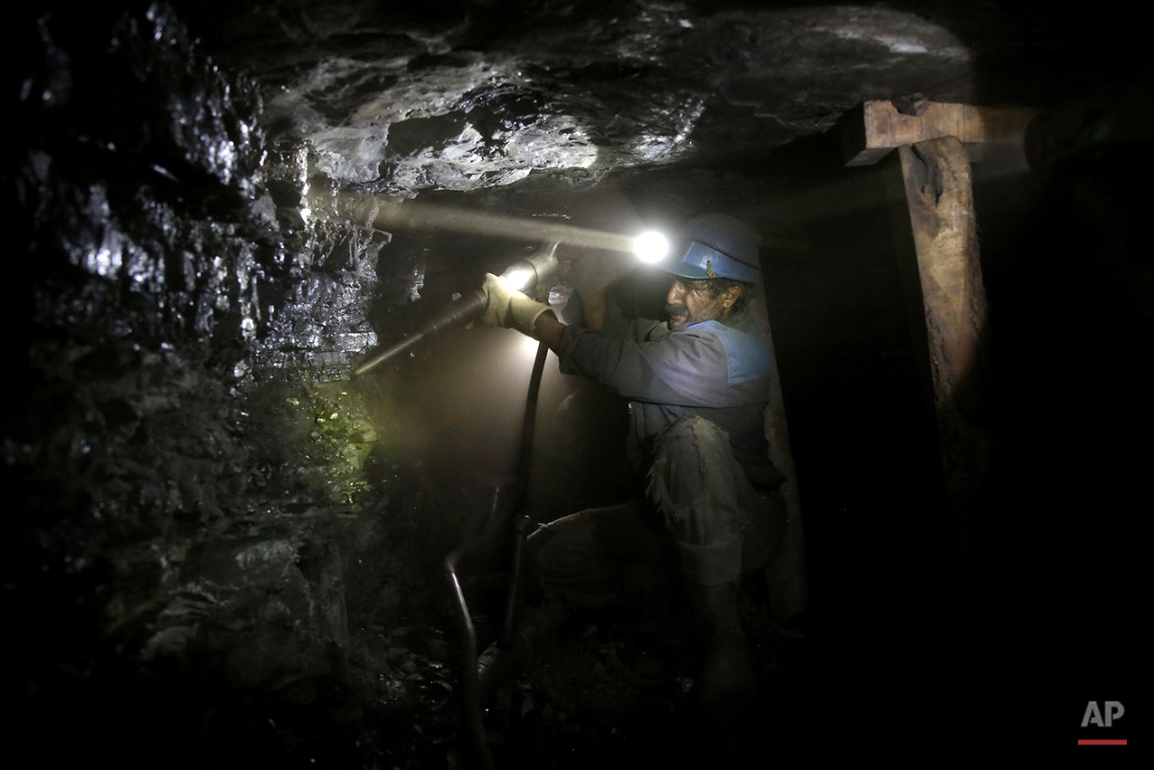 In this Monday, Aug. 18, 2014 photo, an Iranian coal miner works inside a mine near the city of Zirab 212 kilometers (132 miles) northeast of the capital Tehran, on a mountain in Mazandaran province, Iran. The miners tunnel deep into the mountains, working in dark, narrow passageways where the risk of toxic gases and cave-ins is never far from their minds. (AP Photo/Ebrahim Noroozi)