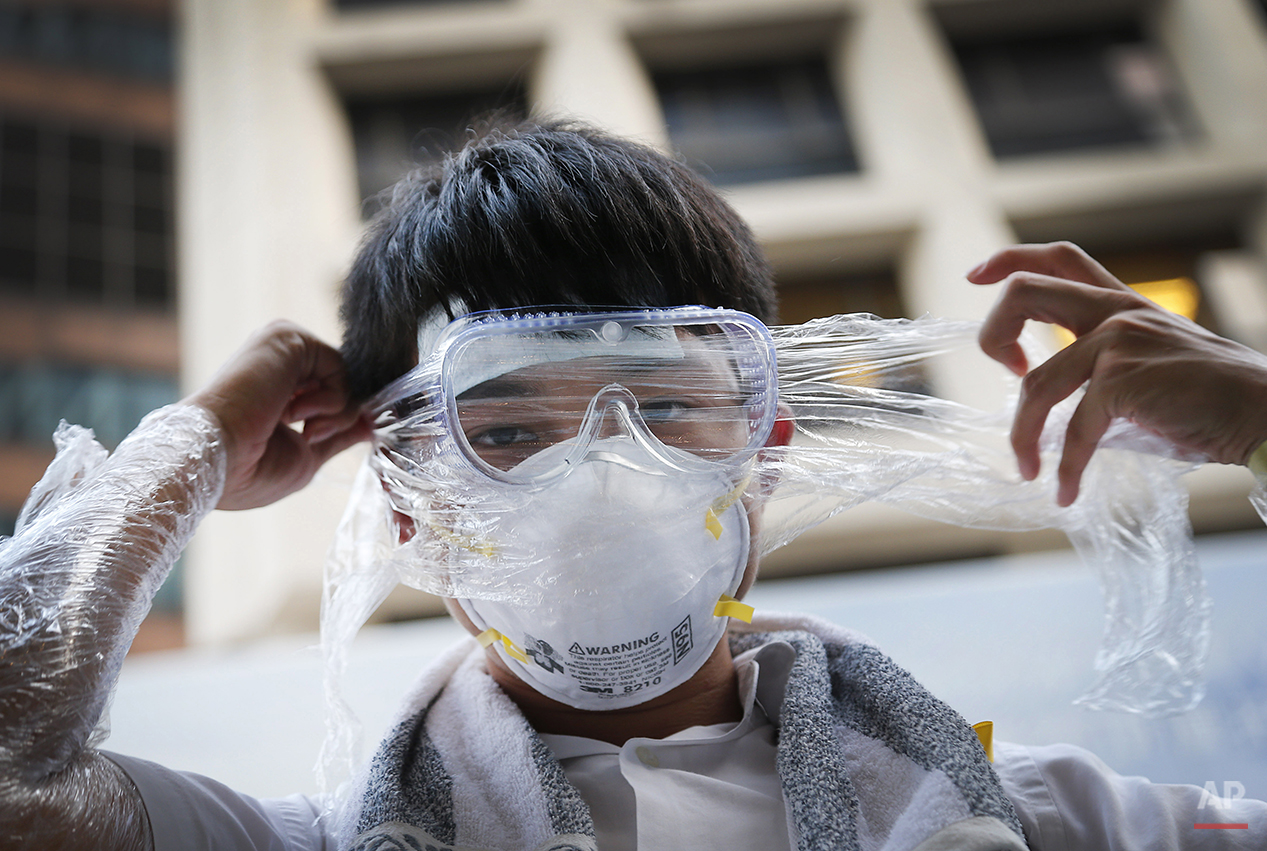 A student pro-democracy protester covers his face in plastic wrap to protect against pepper spray in the event that it is used as they stand-off with local police, Monday, Sept. 29, 2014 in Hong Kong. Pro-democracy protesters expanded their rallies throughout Hong Kong on Monday, defying calls to disperse in a major pushback against Beijing's decision to limit democratic reforms in the Asian financial hub. (AP Photo/Wong Maye-E)