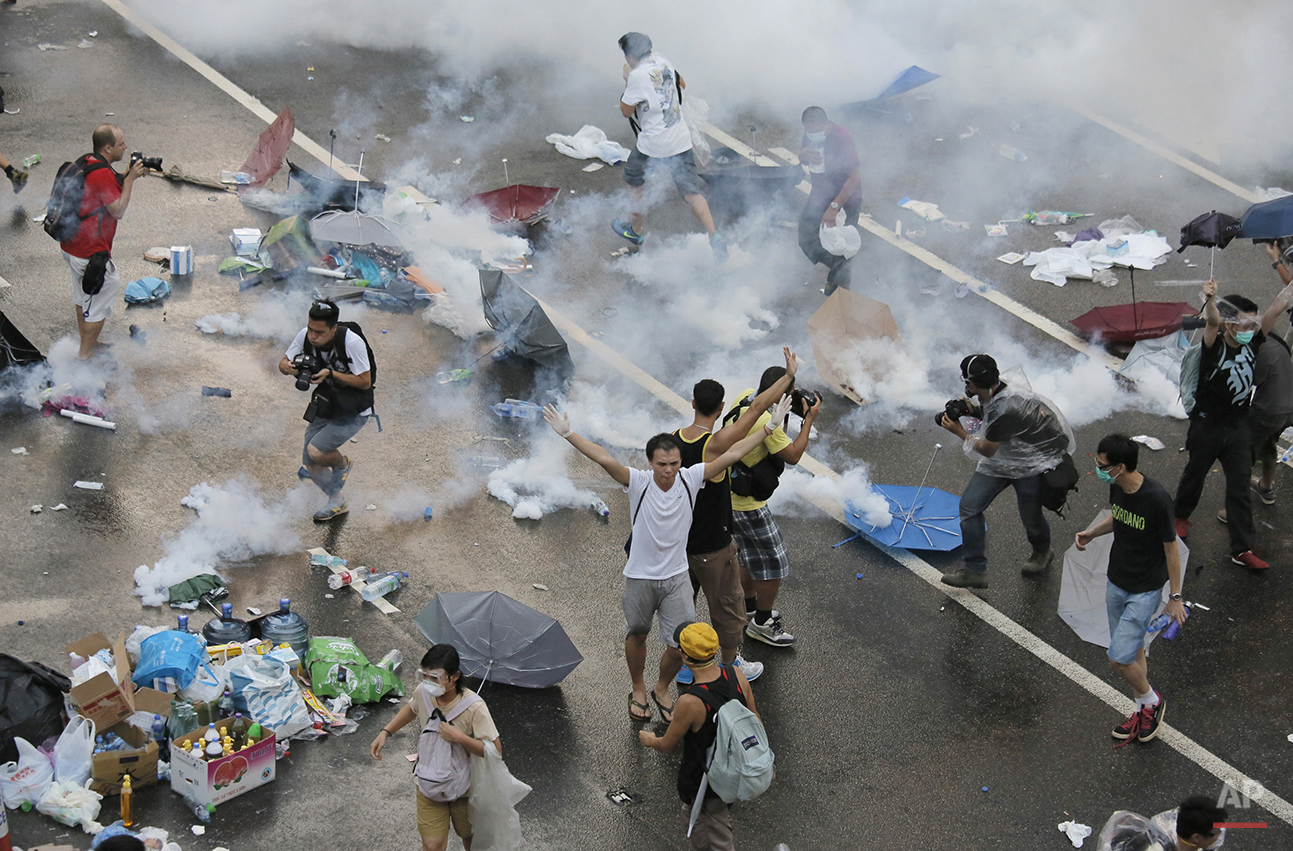 Protesters walk through tear gas used by riot police against protesters after thousands of people blocked a main road at the financial central district in Hong Kong, Sunday, Sept. 28, 2014. Authorities launched their crackdown after the protest spiraled into an extraordinary scene of chaos as the crowd jammed a busy road and clashed with officers wielding pepper spray. (AP Photo/Vincent Yu)
