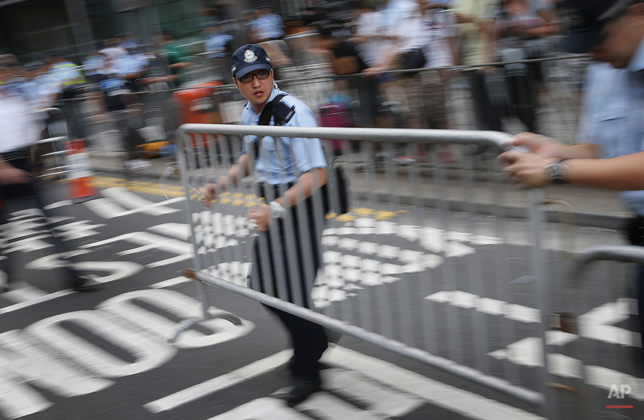 Policemen set up metal barricades in efforts to keep pro-democracy protesters at bay in Hong Kong Monday, Sept. 29, 2014. Protesters expanded their rallies throughout Hong Kong on Monday, defying calls to disperse in a major pushback against Beijing's decision to limit democratic reforms in the Asian financial hub. (AP Photo/Wong Maye-E)