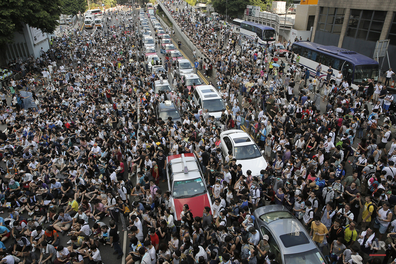 Thousands of people block a main road in Hong Kong, Sunday, Sept. 28, 2014. Hong Kong activists kicked off a long-threatened mass civil disobedience protest Sunday to challenge Beijing over restrictions on voting reforms, escalating the battle for democracy in the former British colony after police arrested dozens of student demonstrators. (AP Photo/Vincent Yu)