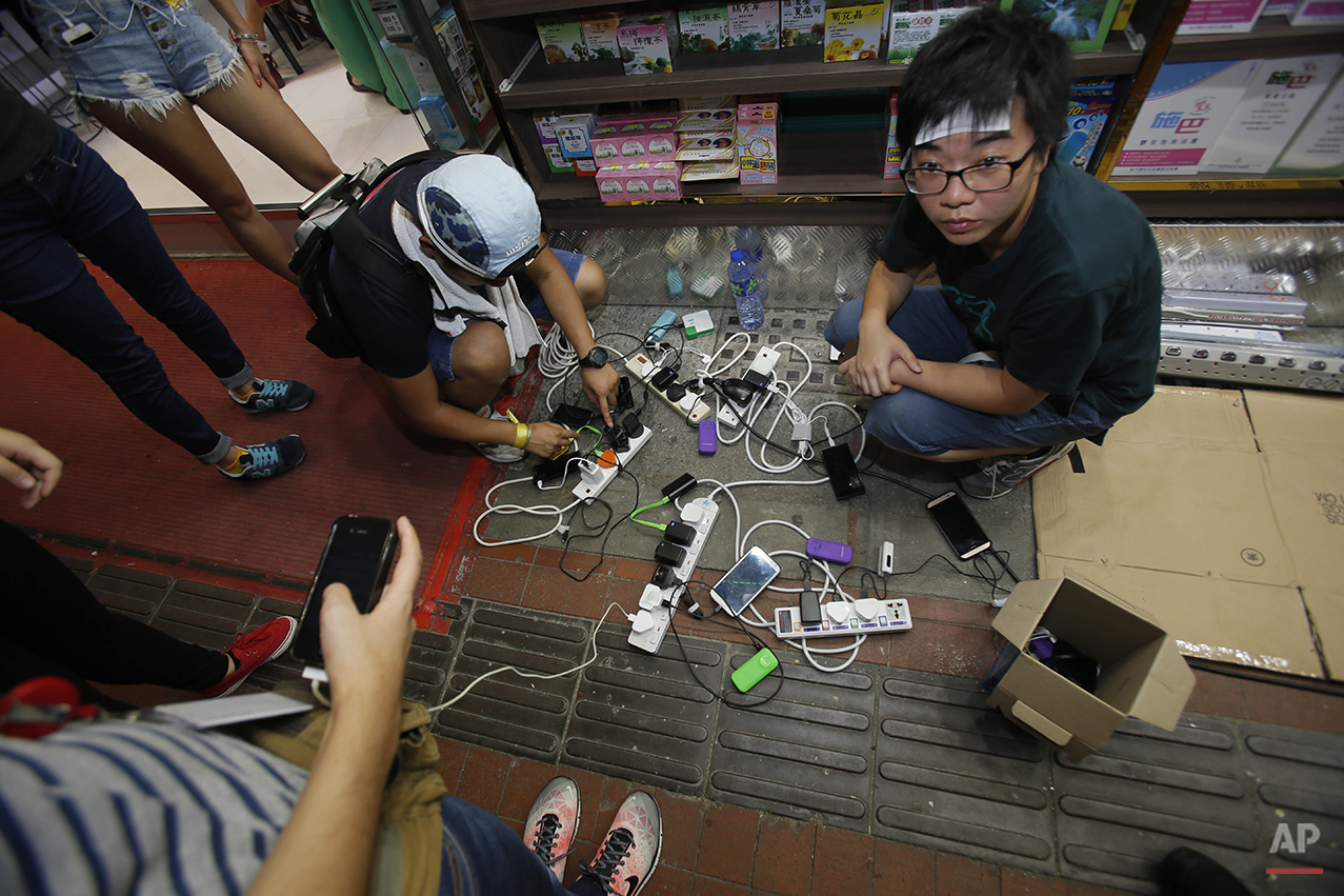 Student protesters connect electric extension cords to charge their phones during a sit-in protest in Hong Kong, Monday, Sept. 29, 2014. Pro-democracy protesters expanded their rallies throughout Hong Kong on Monday, defying calls to disperse in a major pushback against Beijing's decision to limit democratic reforms in the Asian financial hub. (AP Photo/Wally Santana)