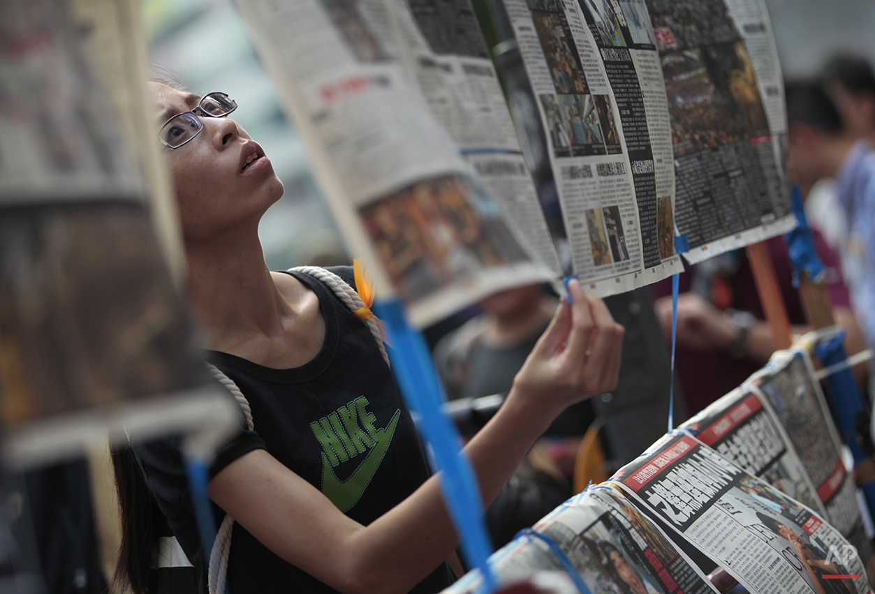 A woman reads the latest newspaper articles displayed at a sit-in protest in Hong Kong, Monday, Sept. 29, 2014. Pro-democracy protesters expanded their rallies throughout Hong Kong on Monday, defying calls to disperse in a major pushback against Beijing's decision to limit democratic reforms in the Asian financial hub. (AP Photo/Wally Santana)