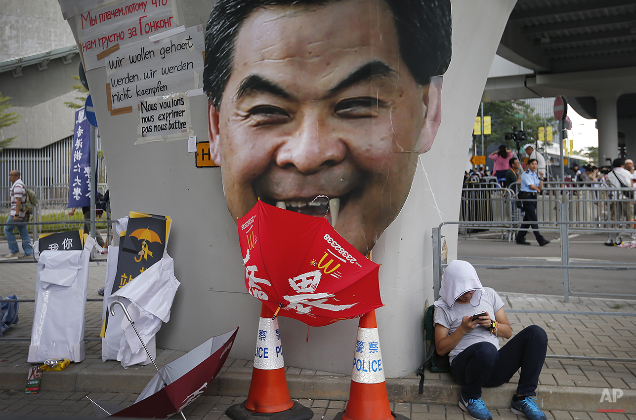 A student protester rests next to a defaced cut-out of Hong Kong's Chief Executive Leung Chun-ying at one of their protest sites around the government headquarters, Tuesday, Sept. 30, 2014, in Hong Kong. Pro-democracy protesters in Hong Kong set a Wednesday deadline for the city's unpopular Chief Executive Leung Chun-ying to meet their demands for genuine democracy and for him to step down as leader of Hong Kong, after spending another night blocking streets in an unprecedented show of civil disobedience. (AP Photo/Wong Maye-E)